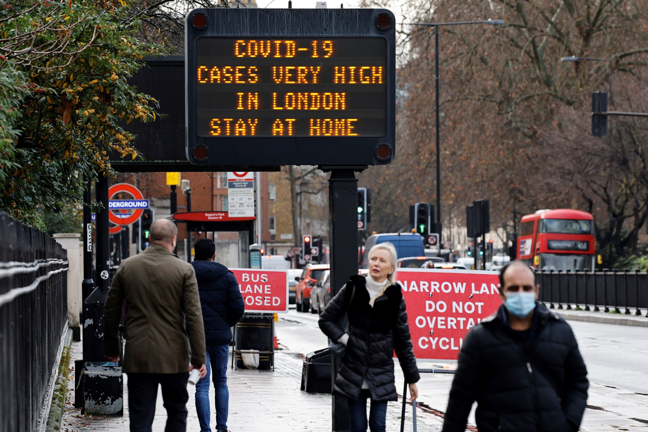Pedestrians, some wearing a face mask or covering due to the pandemic, walk past a sign alerting people that coronavirus cases are on the rise in central London on Wednesday. (Tolga Akmen/AFP via Getty Images)