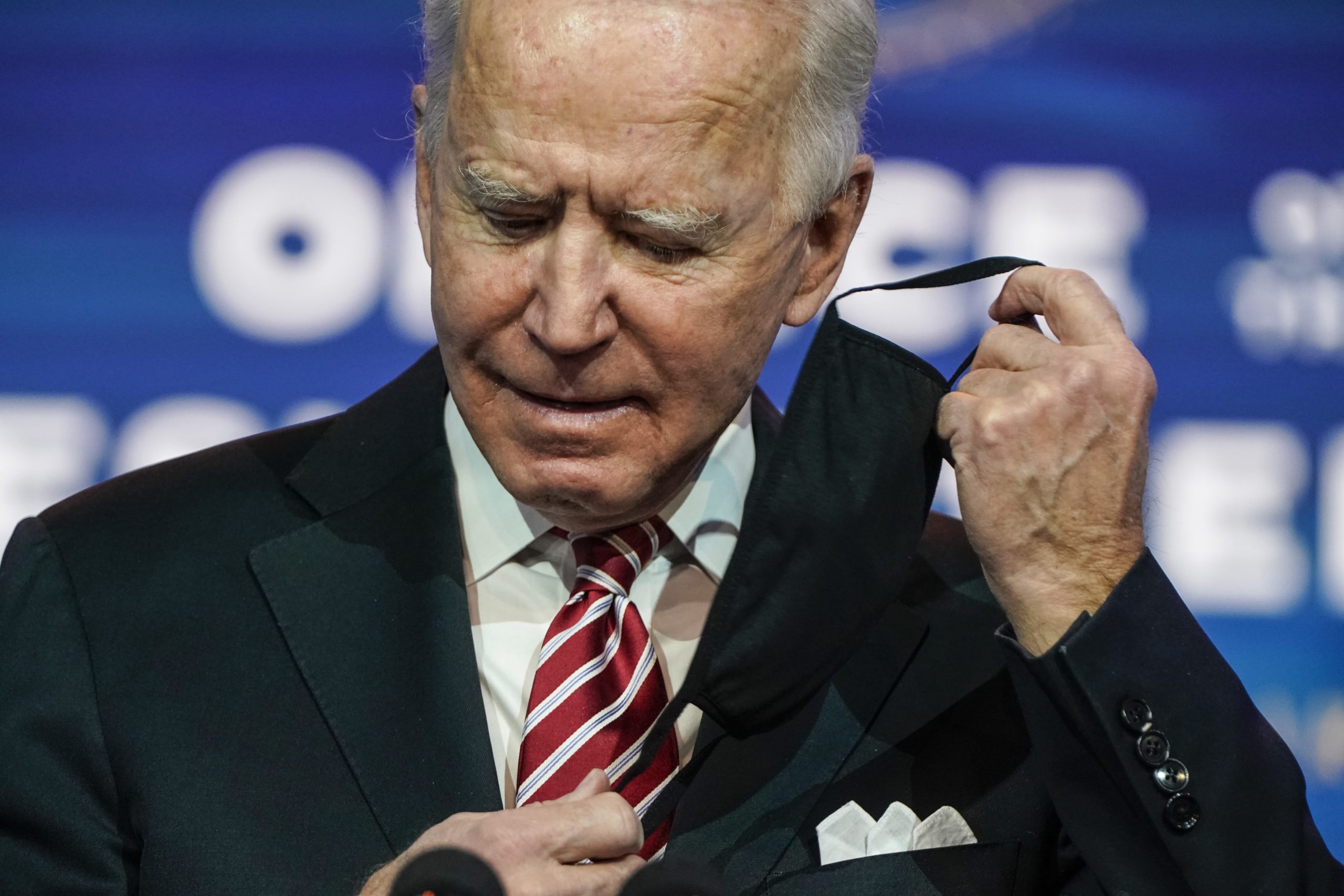 WILMINGTON, DE - DECEMBER 23: President-elect Joe Biden removes his mask before announcing Miguel Cardona as his nominee for Education Secretary at the Queen theatre on December 23, 2020 in Wilmington, Delaware. Cardona, the Connecticut Education Commissioner, will face the urgent task of planning to reopen schools safely during the COVID-19 pandemic. (Photo by Joshua Roberts/Getty Images)