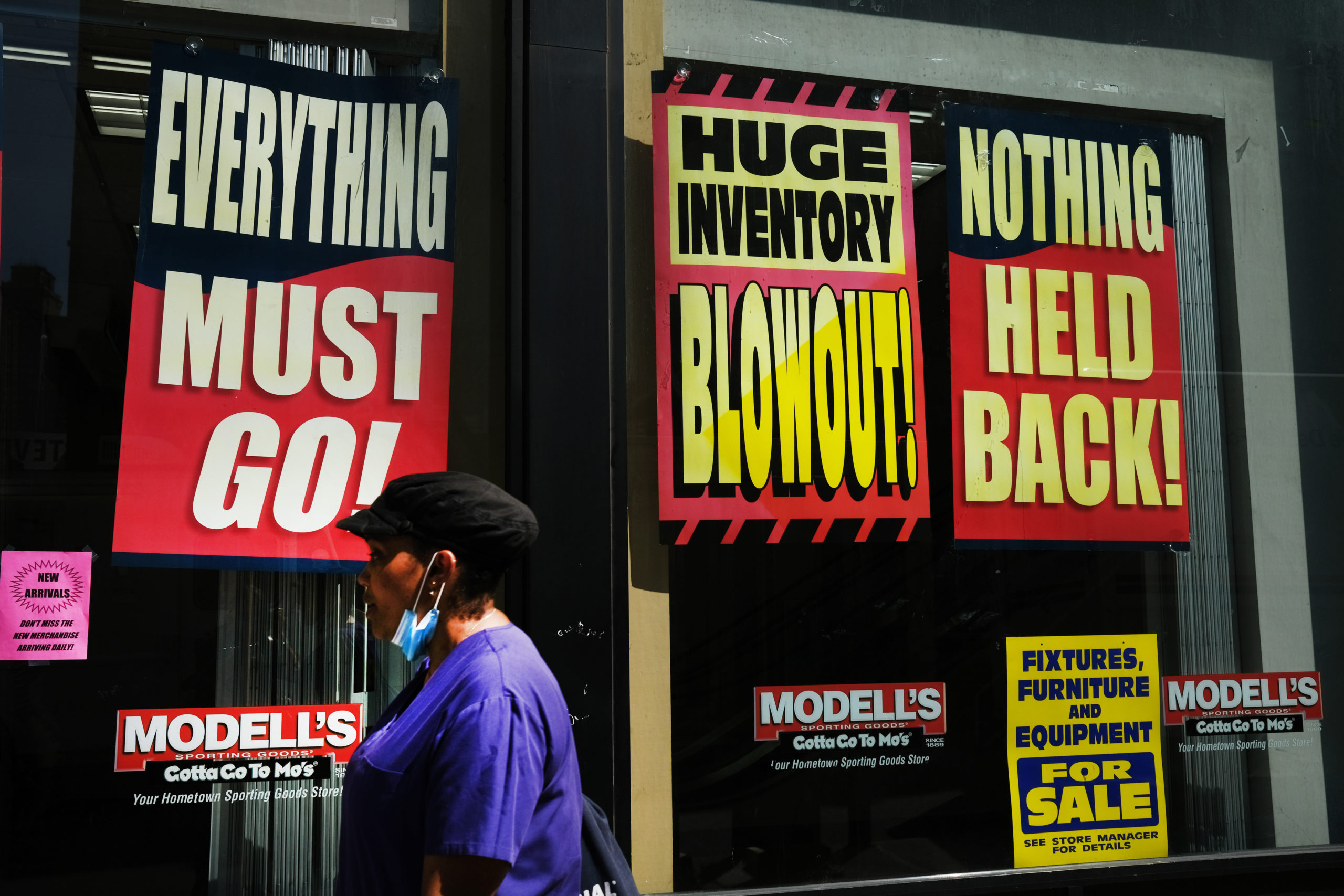 A woman walks by a closed business on July 21 in the Brooklyn borough of New York City. (Spencer Platt/Getty Images)