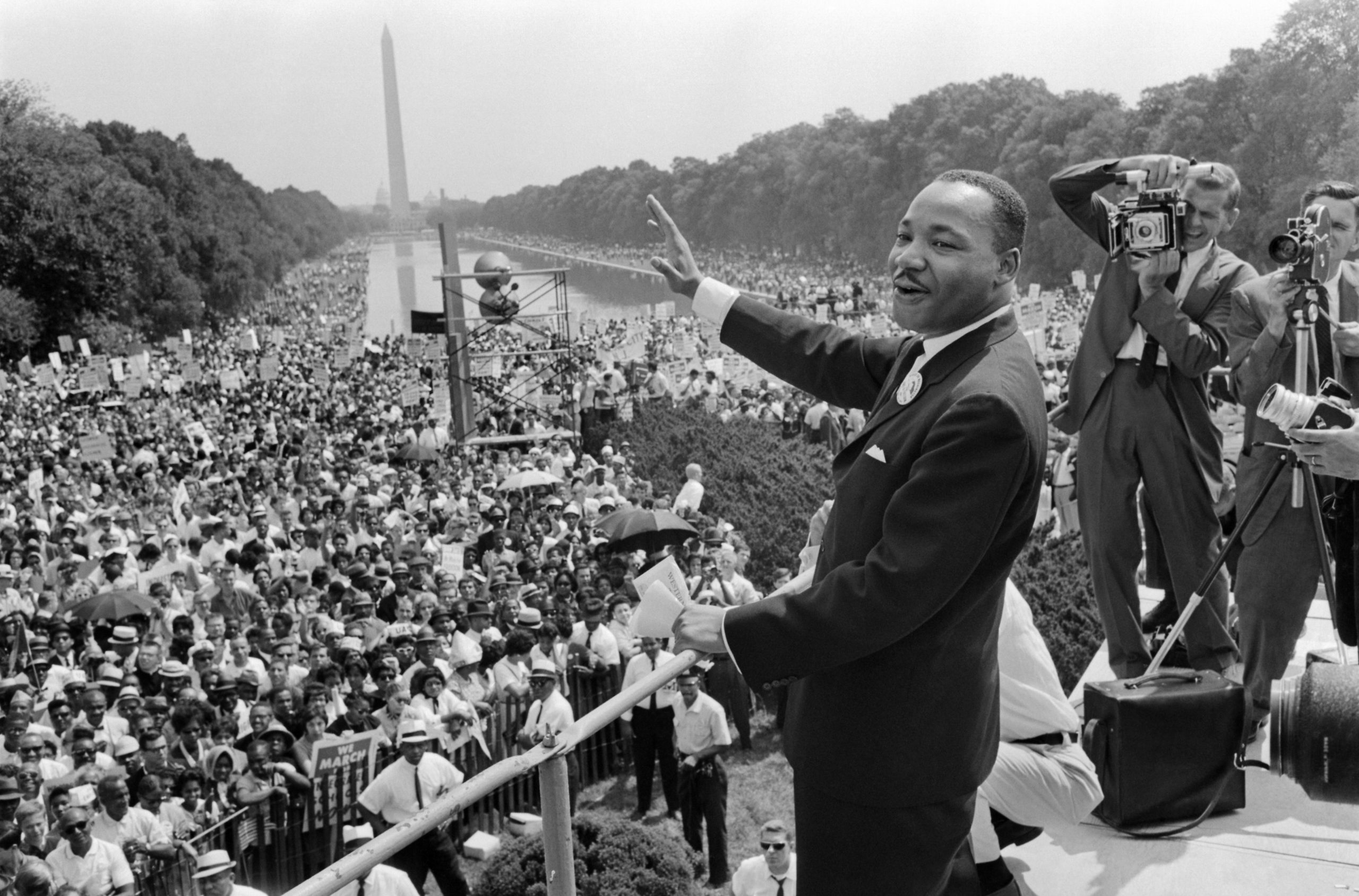 """The civil rights leader Martin Luther King (C) waves to supporters 28 August 1963 on the Mall in Washington DC (Washington Monument in background) during the """"March on Washington"""".( -/AFP via Getty Images)"""