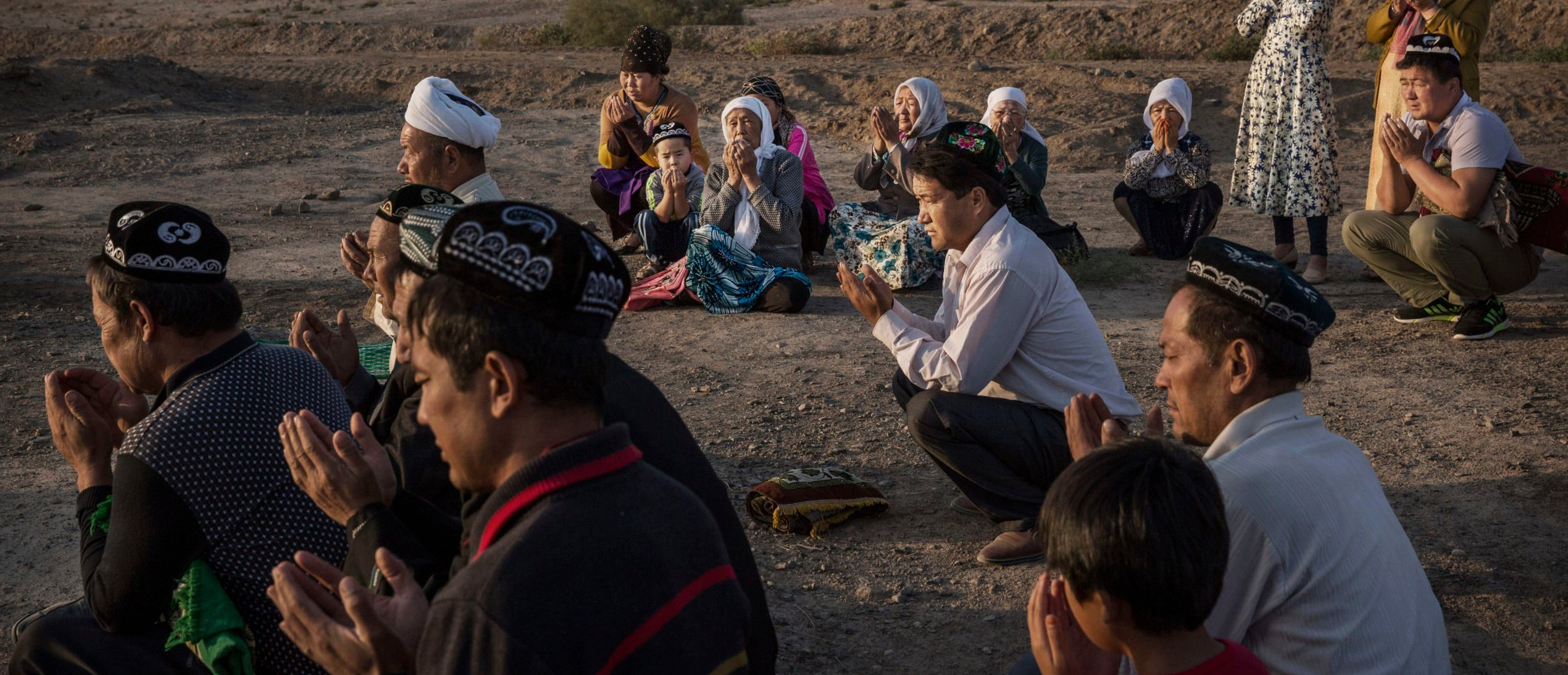 TURPAN, CHINA - SEPTEMBER 12: (CHINA OUT) A Uyghur family pray at the grave of a loved one on the morning of the Corban Festival on September 12, 2016 at a local shrine and cemetery in Turpan County, in the far western Xinjiang province, China.The Corban festival, known to Muslims worldwide as Eid al-Adha or 'feast of the sacrifice', is celebrated by ethnic Uyghurs across Xinjiang, the far-western region of China bordering Central Asia that is home to roughly half of the country's 23 million Muslims. The festival, considered the most important of the year, involves religious rites and visits to the graves of relatives, as well as sharing meals with family. Although Islam is a 'recognized' religion in the constitution of officially atheist China, ethnic Uyghurs are subjected to restrictions on religious and cultural practices that are imposed by China's Communist Party. Ethnic tensions have fueled violence that Chinese authorities point to as justification for the restrictions. (Photo by Kevin Frayer/Getty Images)