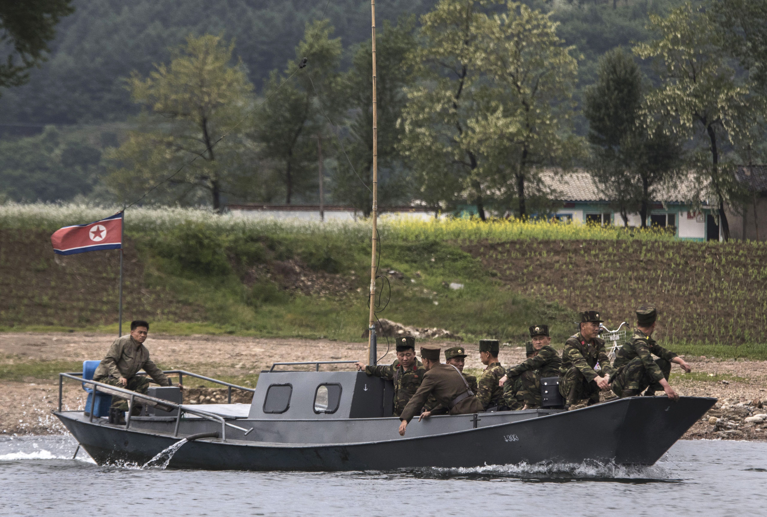 DANDONG, CHINA - MAY 23: (CHINA OUT) North Korean soldiers ride on a boat used as a local ferry as they cross the Yalu river north of the border city of Dandong, Liaoning province, northern China near Sinuiju, North Korea on May 23, 2017 in Dandong, China. China has long been North Korea's main ally and trading partner, but relations are increasingly strained by continued missile testing and provocations by the regime of Kim Jong Un. The North is almost entirely dependent on trade with China to feeds its impoverished economy, yet it has ignored calls by the international community to halt its nuclear and ballistic missile weapons programs. At least three-quarters of trade between the two nations flows through points along its 880-mile long shared border, a divide that reveals stark contrasts in development. Cities such as Dandong boast high-rise buildings and advanced infrastructure, and the Friendship Bridge serves as the conduit for the bulk of trade. From hired boats along the Yalu river, Chinese tourists peer into the reclusive North, marked by soldiers, meagre villages, and depleted farmland. The United States has pressured China to do more to leverage its clout with North Korea, though Beijing remains concerned that outright regime collapse in Pyongyang could trigger a rush of refugees across the border. (Photo by Kevin Frayer/Getty Images)