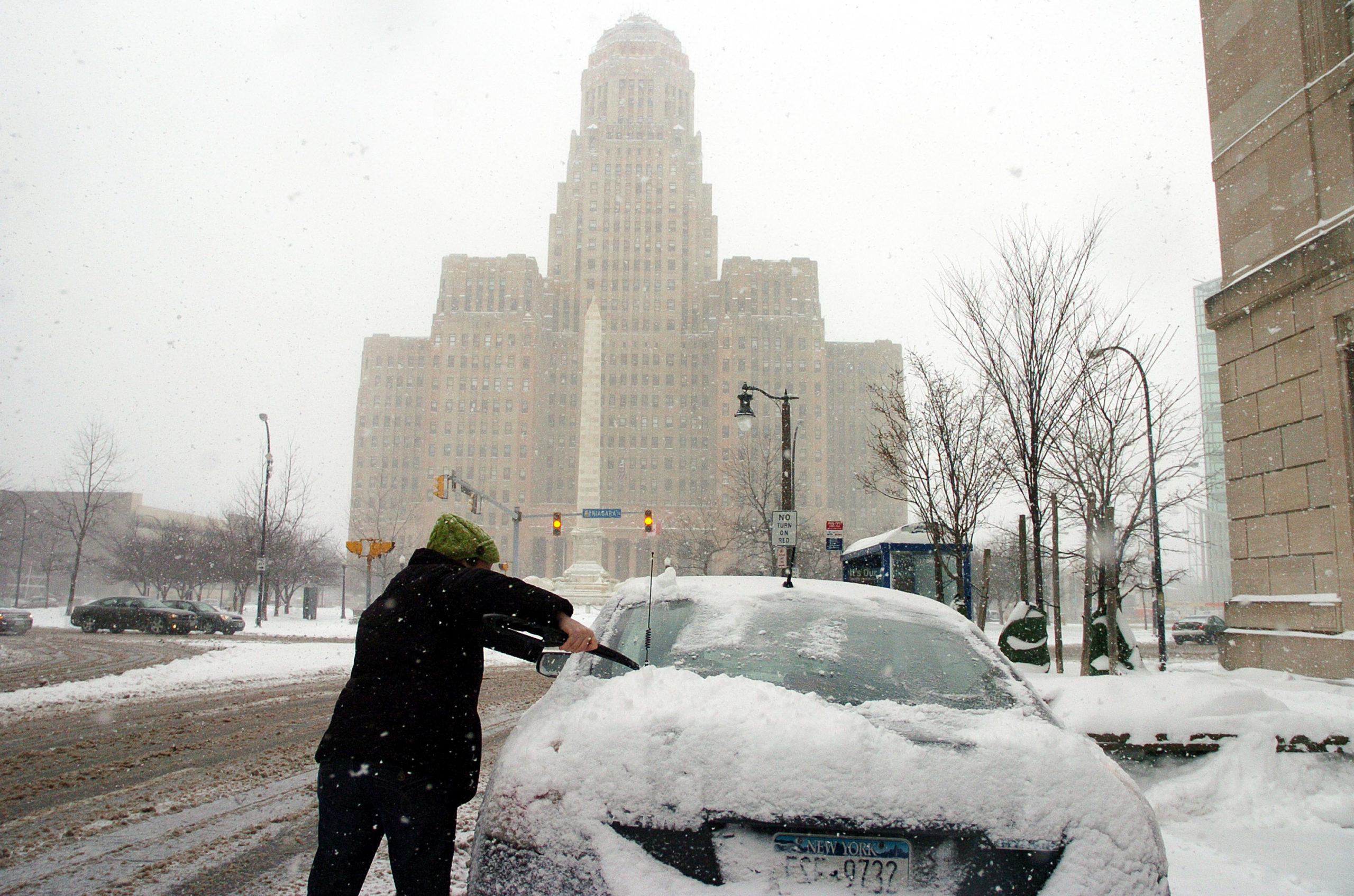 A pedestrian clears their car in front of Buffalo City Hall as lake effect snow bands again set up on December 14, 2010, in Buffalo, New York. (John Normile/Getty Images)