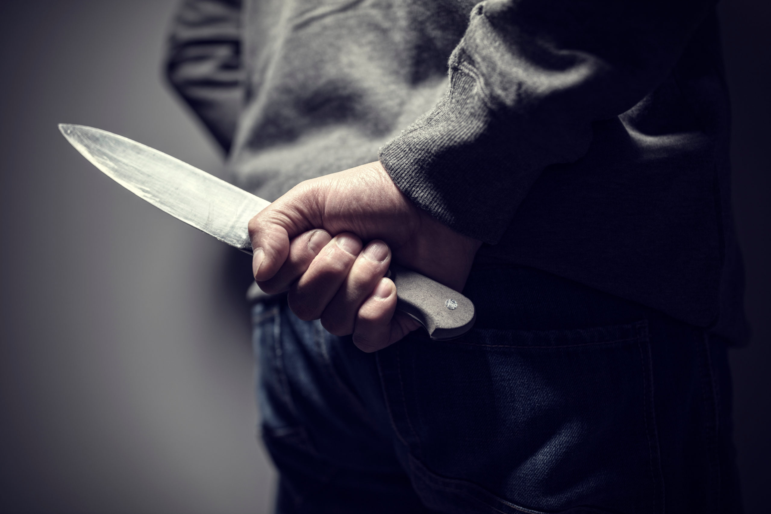 Criminal with knife hidden behind his back (Shutterstock/Brian A Jackson)