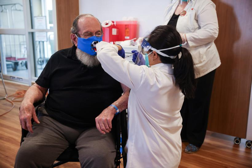 Robert Aucoin, 78, a U.S. Air Force veteran and resident at the Soldiers' Home in Holyoke, receiving the first COVID-19 vaccine at the Home. Photo credit: Leon Nguyen/The Springfield Republican