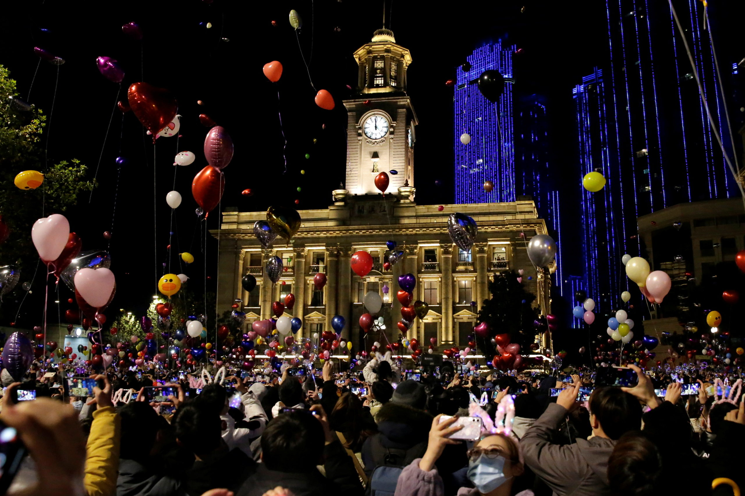 People hold balloons as they gather to celebrate the arrival of the new year, following the coronavirus disease (COVID-19) outbreak, in Wuhan, China December 31, 2020.