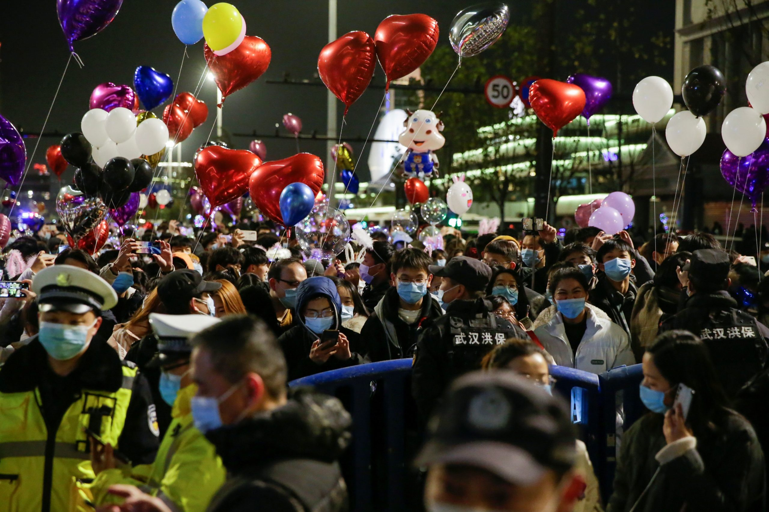 Police officers stand guard as people gather to celebrate the arrival of the new year during the coronavirus disease (COVID-19) outbreak in Wuhan, China December 31, 2020.