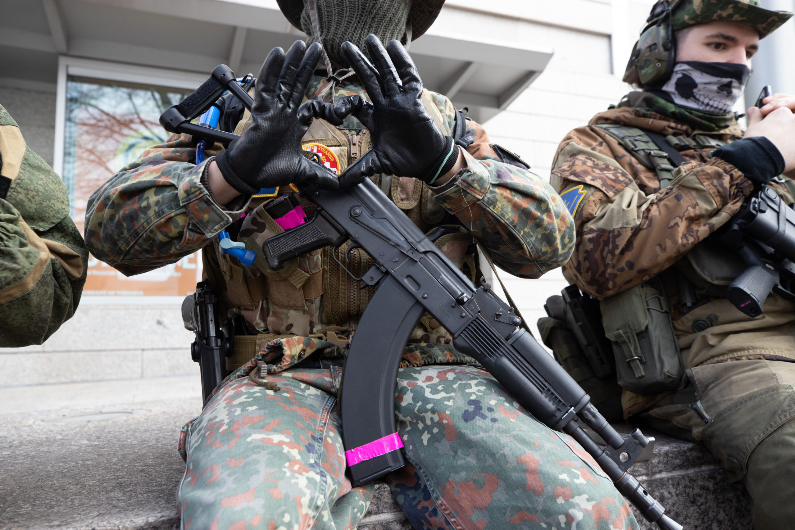 An armed demonstrator made a hand gesture while wearing a patch associated with a 4 Chan board catalog in Richmond, Virginia on January 18, 2021. (Kaylee Greenlee - Daily Caller News Foundation)
