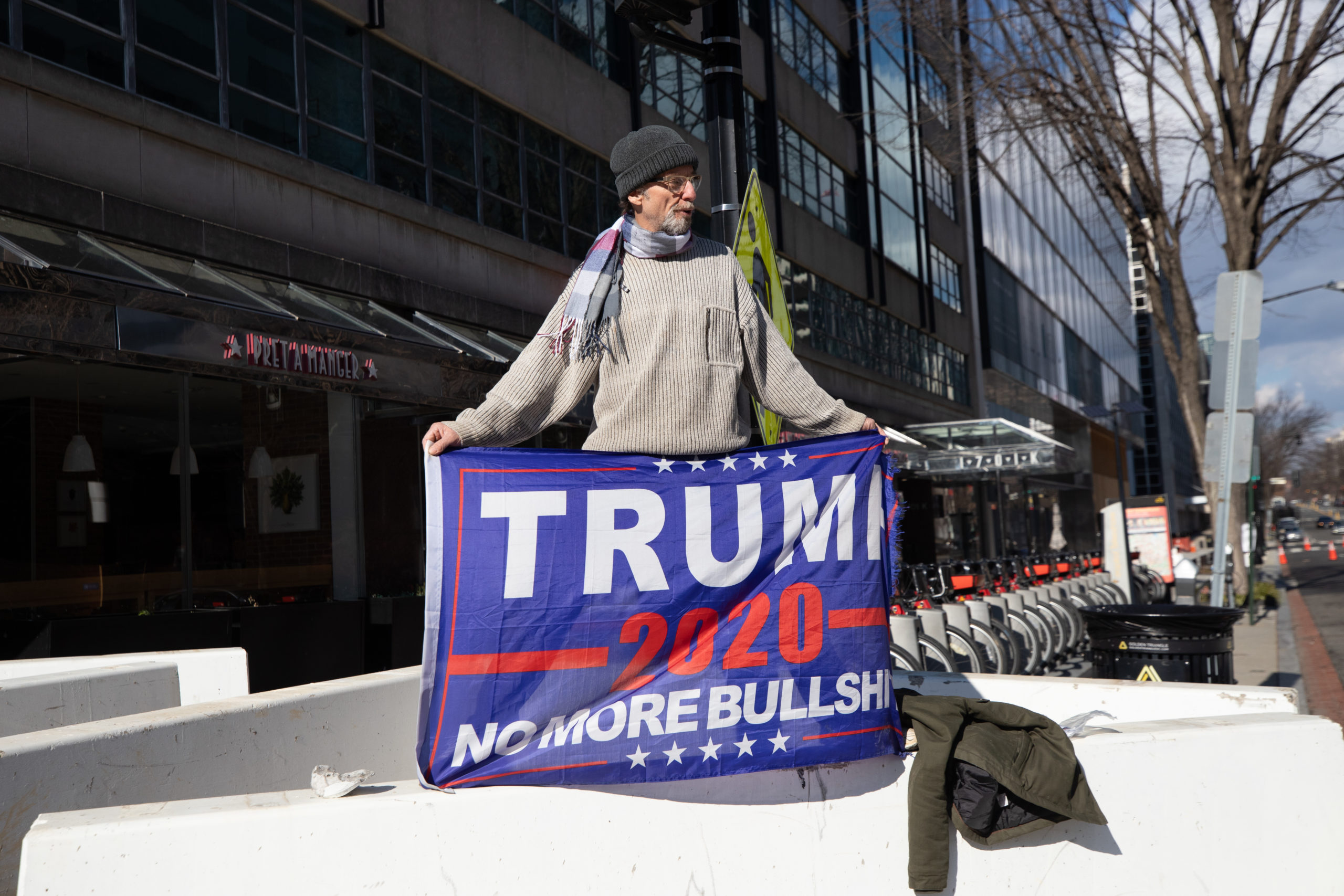 A man named Monty held a Trump flag while standing on a concrete barrier near Black Lives Matter Plaza in Washington, D.C. on Jan. 20, 2021. (Kaylee Greenlee - Daily Caller News Foundation)