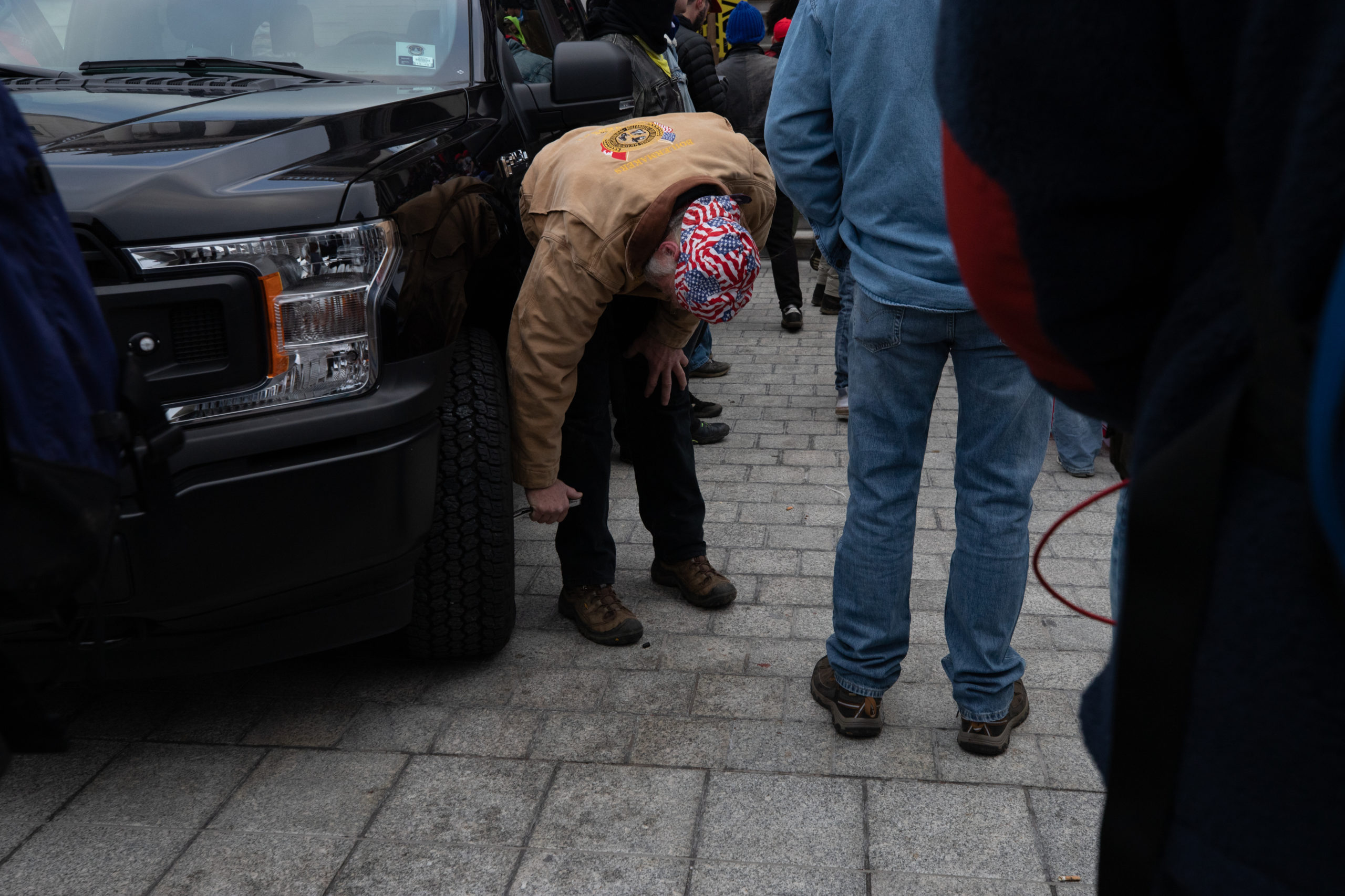 A demonstrator slashed the tires on law enforcement vehicles in Washington, D.C. on Jan. 6, 2021. (Kaylee Greenlee – Daily Caller News Foundation)