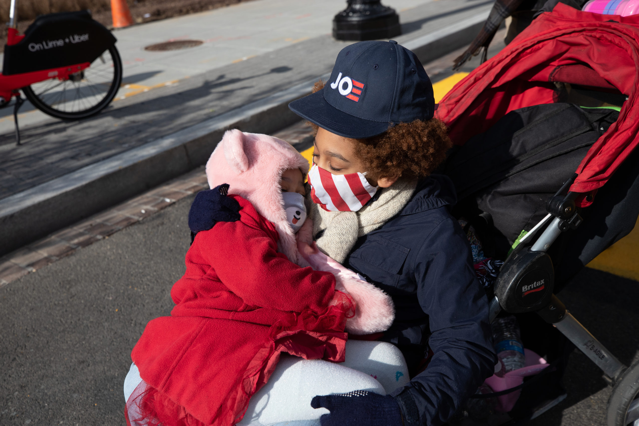 Two children hugged in a stroller in Black Lives Matter Plaza in Washington, D.C. on Jan. 20, 2021. (Kaylee Greenlee - Daily Caller News Foundation)