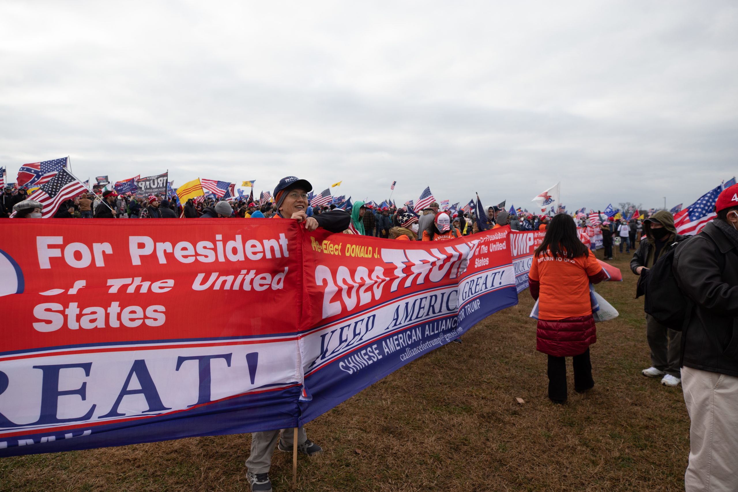 A man stood behind a long line of banners expressing support for President Donald Trump by the Chinese American Alliance in Washington, D.C. on Jan. 6, 2021. (Kaylee Greenlee - Daily Caller News Foundation)