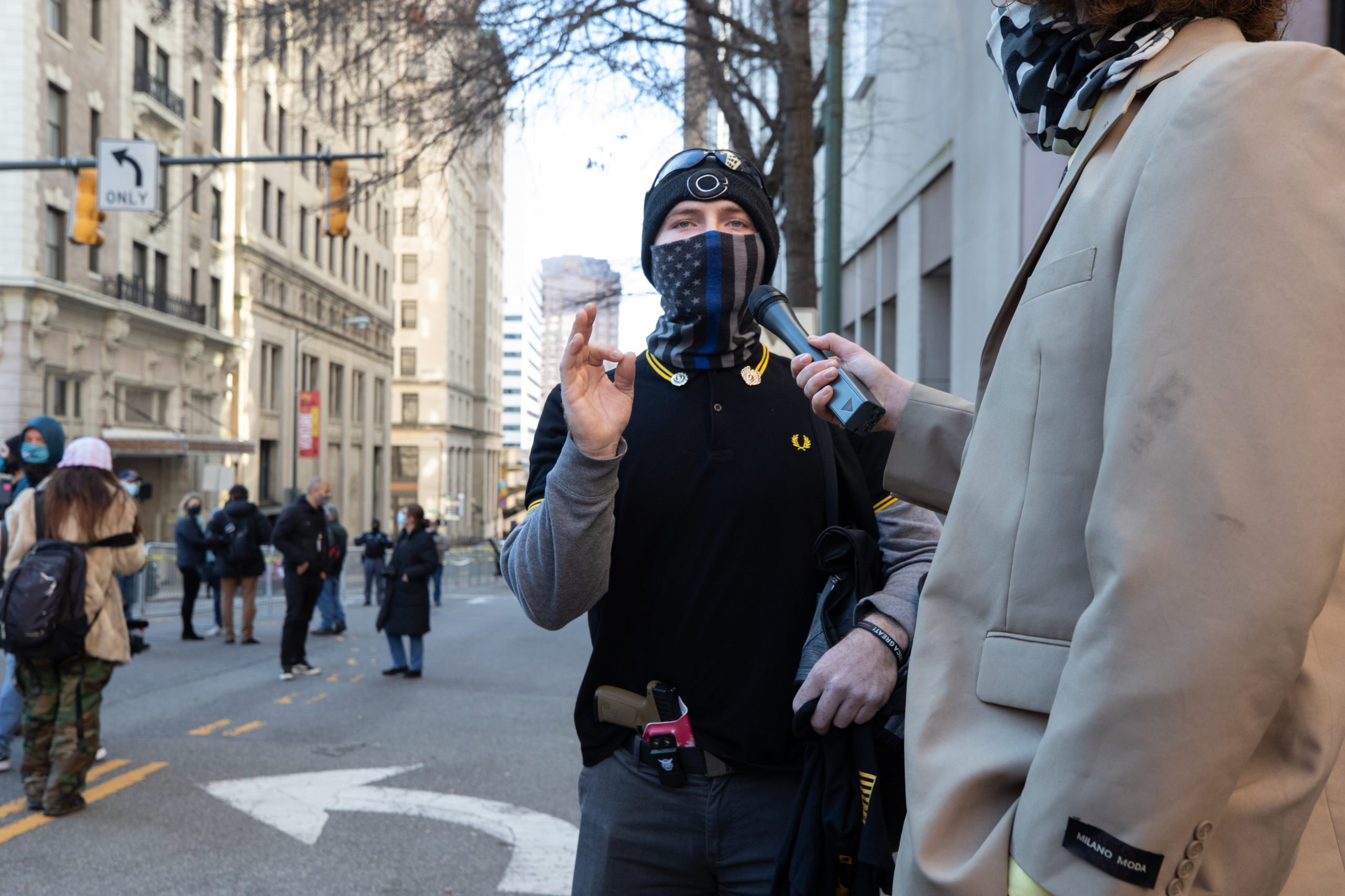 """An armed Proud Boy made a hand gesture while wearing a """"thin blue line"""" face mask, a Proud Boy polo shirt, and a holstered handgun in Richmond, Virginia on January 18, 2021. (Kaylee Greenlee - Daily Caller News Foundation)"""
