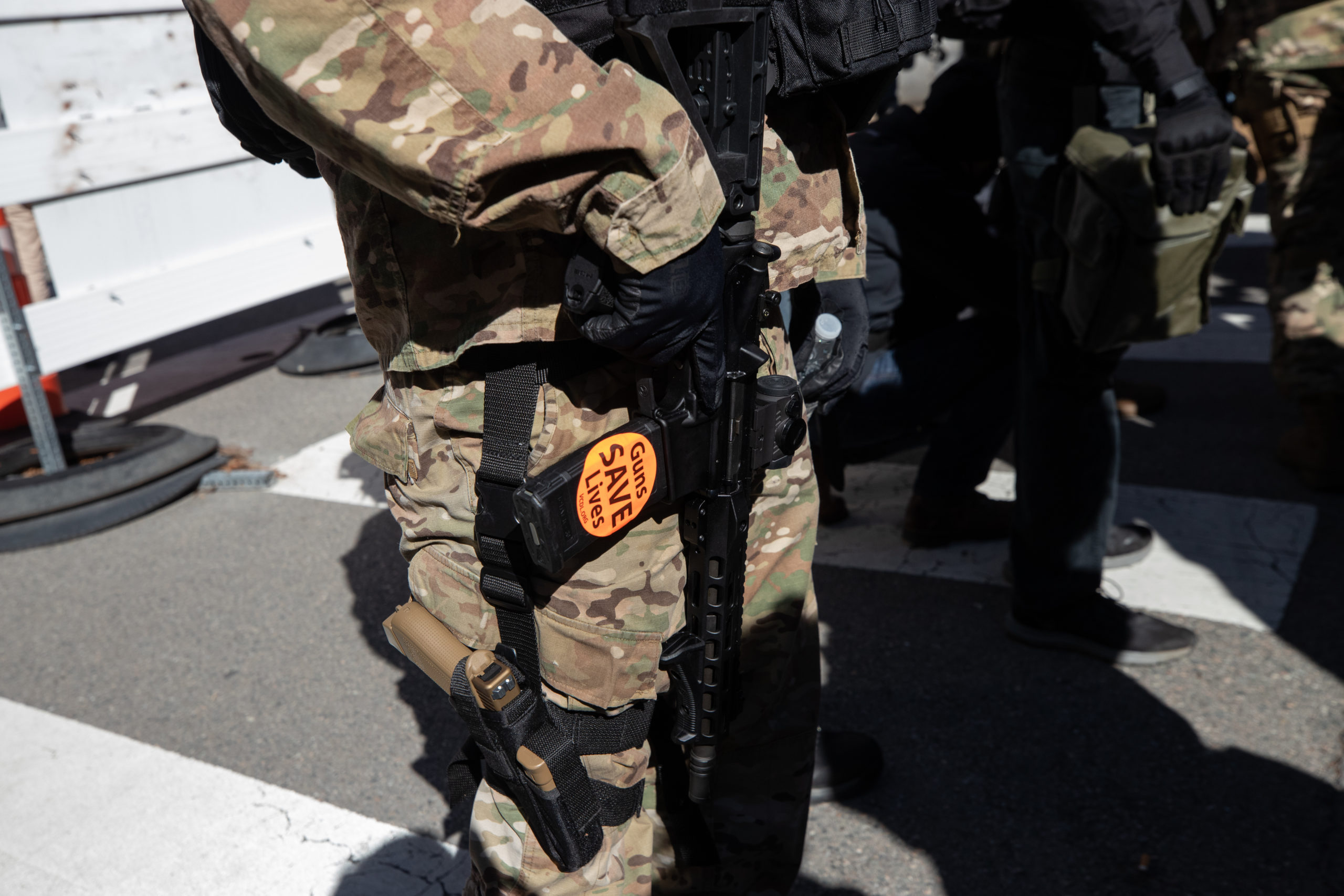 """An armed demonstrator held a rifle with a """"guns save lives"""" sticker on the magazine during Lobby Day demonstrations in Richmond, Virginia on January 18, 2021. (Kaylee Greenlee - Daily Caller News Foundation)"""