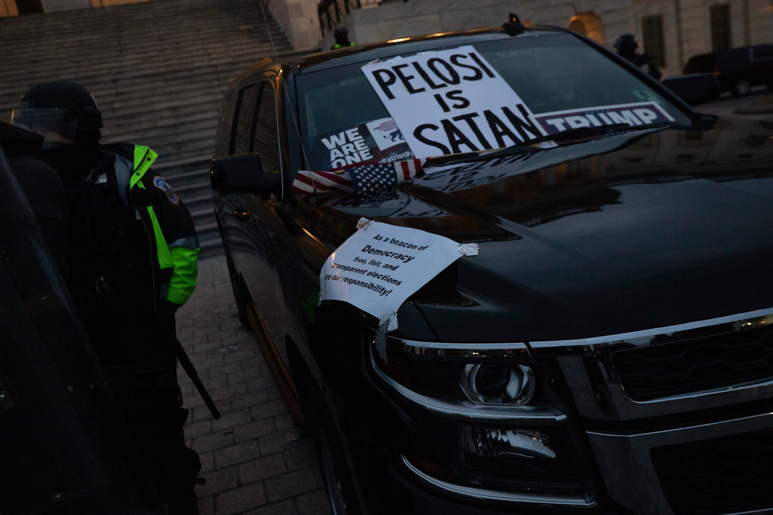 A sign calling Pelosi satan and an American flag were draped over a government vehicle in Washington, D.C. on Jan. 6, 2021. (Kaylee Greenlee - Daily Caller News Foundation)