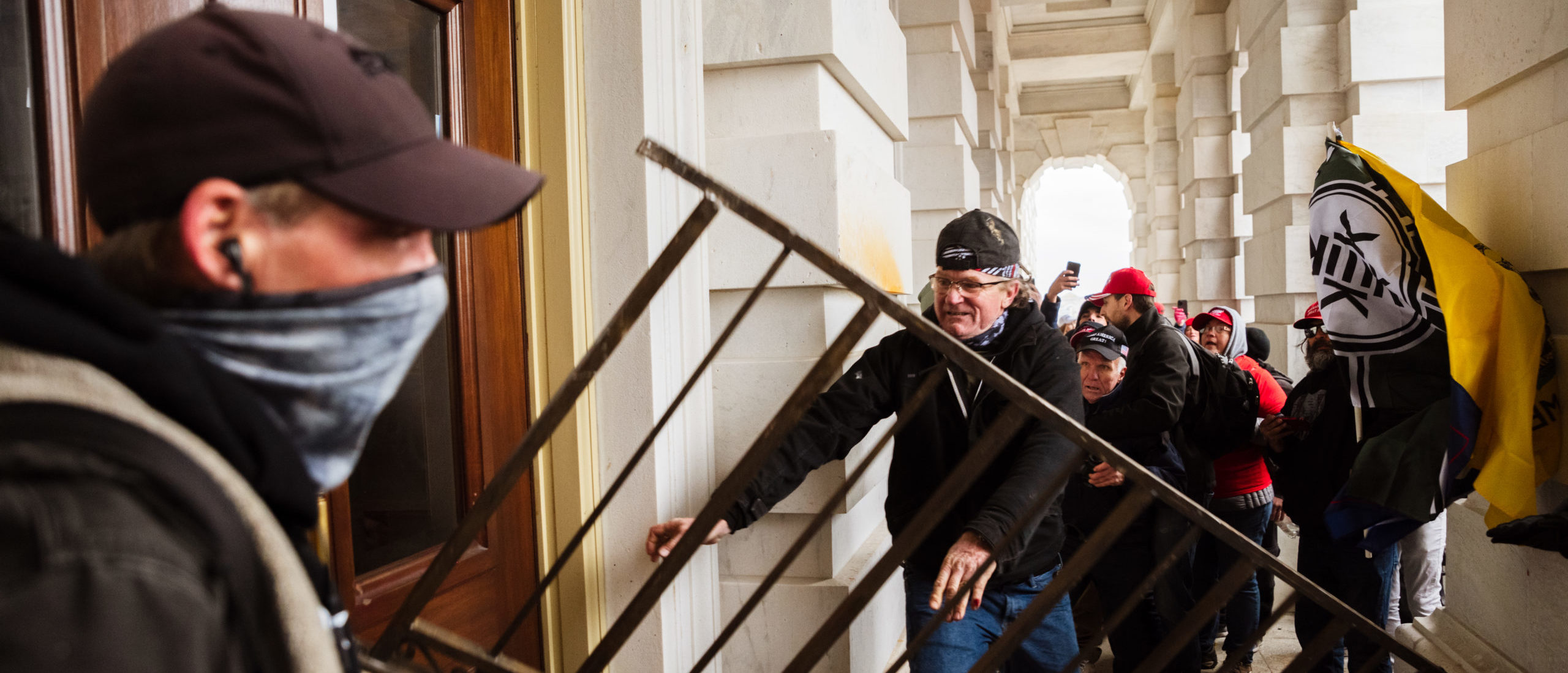A member of a pro-Trump mob bashes an entrance of the Capitol Building in an attempt to gain access on January 6, 2021 in Washington, DC.