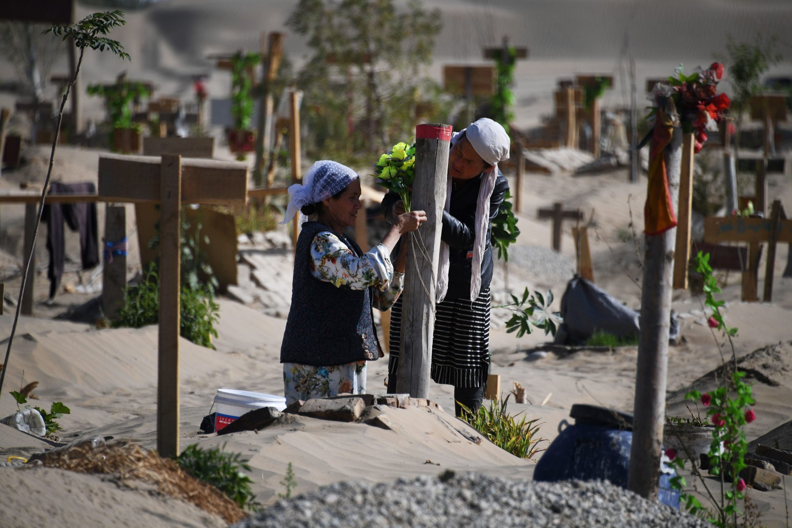 """TOPSHOT - This photo taken on May 31, 2019 shows two women decorating a grave in a Uighur graveyard on the outskirts of Hotan in China's northwest Xinjiang region. - China has enforced a massive security crackdown in Xinjiang, where more than one million ethnic Uighurs and other mostly Muslim minorities are believed to be held in a network of internment camps that Beijing describes as """"vocational education centres"""" aimed at steering people away from religious extremism. (Photo by Greg Baker / AFP) (Photo credit should read GREG BAKER/AFP via Getty Images)"""