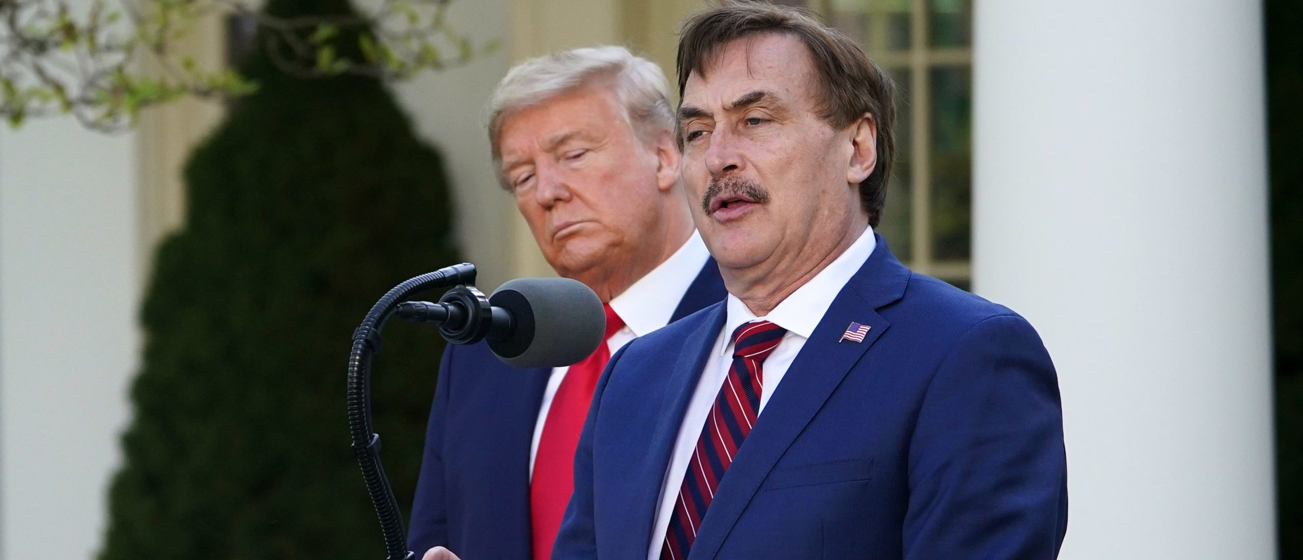 US President Donald Trump listens as Michael J. Lindell, CEO of MyPillow Inc., speaks during the daily briefing on the novel coronavirus, COVID-19, in the Rose Garden of the White House in Washington, DC, on March 30, 2020. (Photo by MANDEL NGAN / AFP) (Photo by MANDEL NGAN/AFP via Getty Images)
