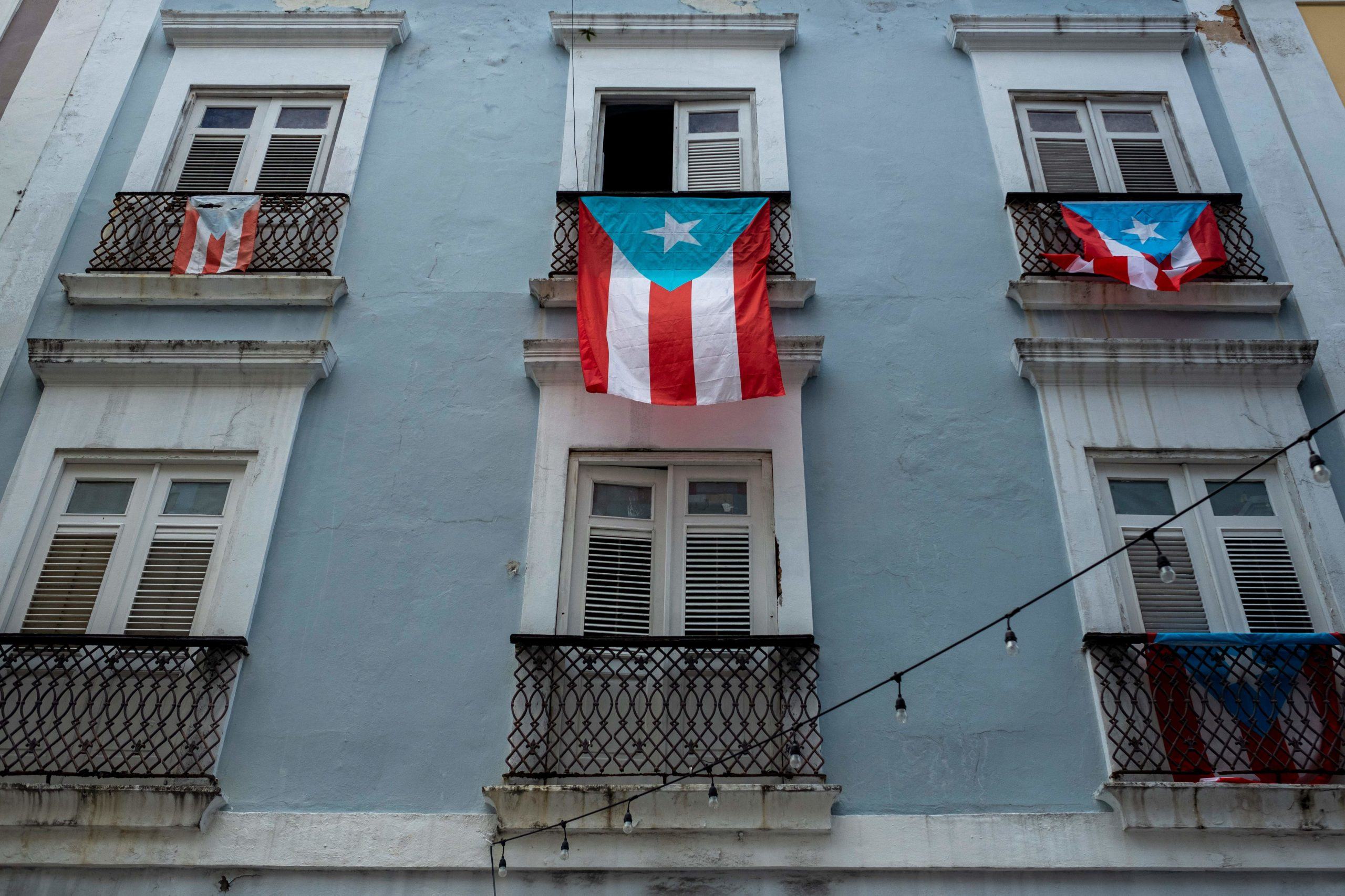 Puerto Rican National flags hang from balconies in Old San Juan, Puerto Rico on April 7, 2020. (Ricardo Arduengo/AFP via Getty Images)