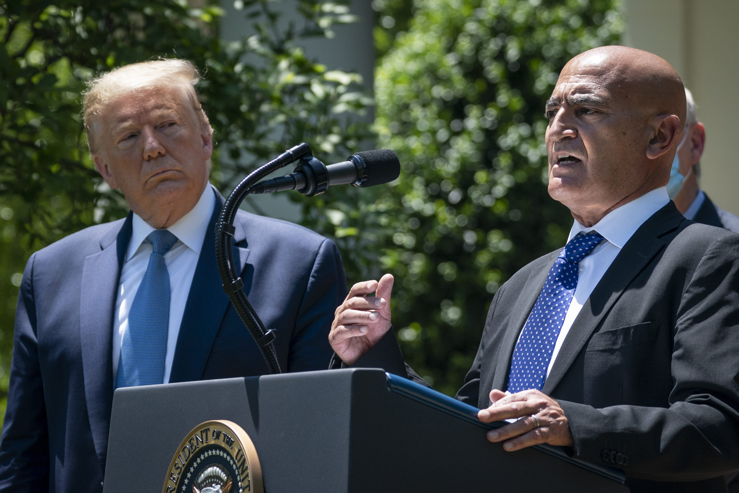 "WASHINGTON, DC - MAY 15: (L-R) U.S. President Donald Trump listens as Moncef Slaoui, the former head of GlaxoSmithKlines vaccines division, speaks about coronavirus vaccine development in the Rose Garden of the White House on May 15, 2020 in Washington, DC. Dubbed ""Operation Warp Speed,"" the Trump administration is announcing plans for an all-out effort to produce and distribute a coronavirus vaccine by the end of 2020. (Photo by Drew Angerer/Getty Images)"