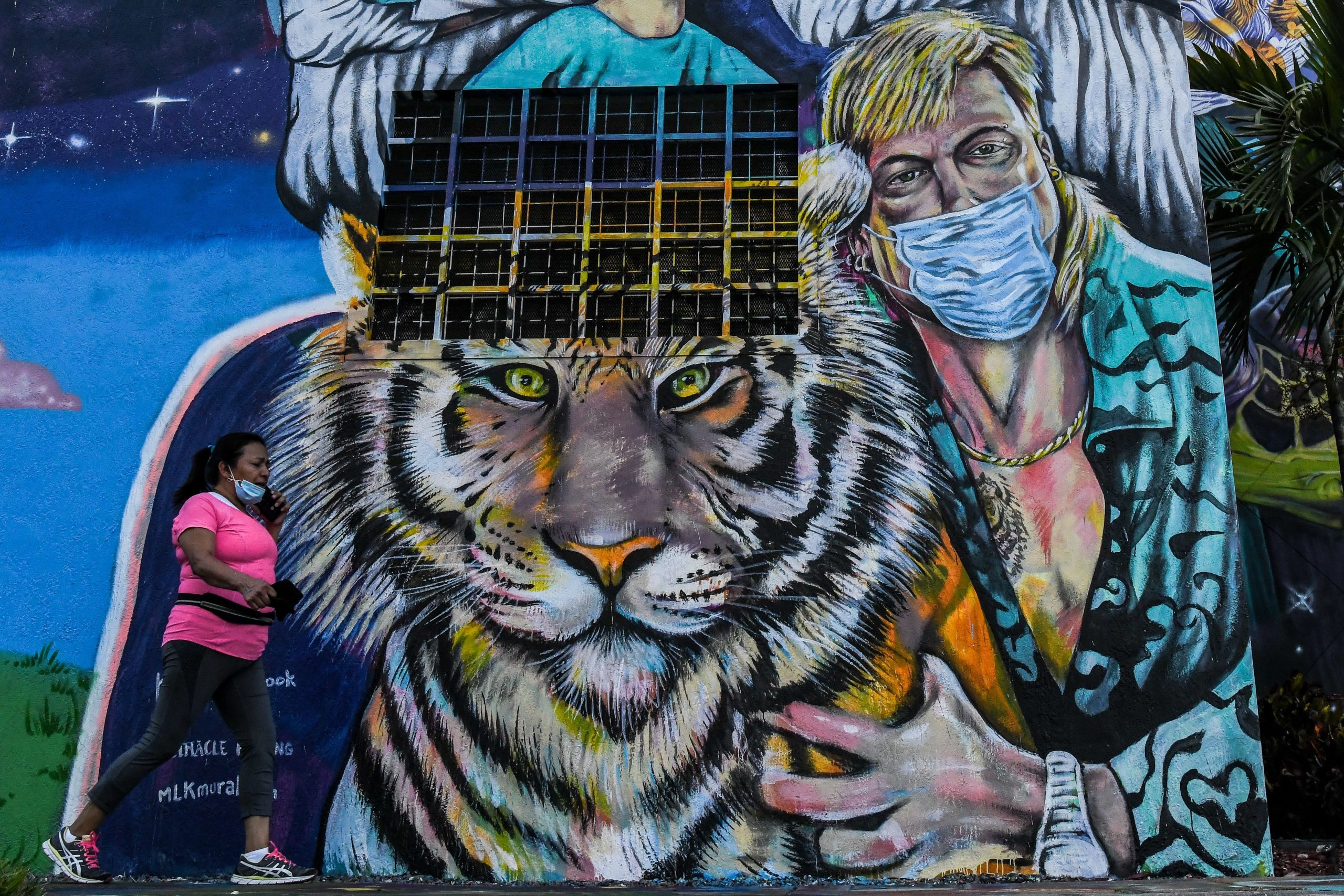 "A woman walks past a mural by US muralist Kyle Holbrook with health workers and Joseph ""Joe Exotic"" Maldonado-Passage (R, below) wearing a mask in Wynwood Art District in Miami, Florida on June 29, 2020. - The City of Miami issued an emergency order mandating facial coverings be worn in public at all times and until further notice. Officials will start issuing fines of up to $500 for not wearing a mask in public. (Photo by CHANDAN KHANNA / AFP) / RESTRICTED TO EDITORIAL USE - MANDATORY MENTION OF THE ARTIST UPON PUBLICATION - TO ILLUSTRATE THE EVENT AS SPECIFIED IN THE CAPTION (Photo by CHANDAN KHANNA/AFP via Getty Images)"