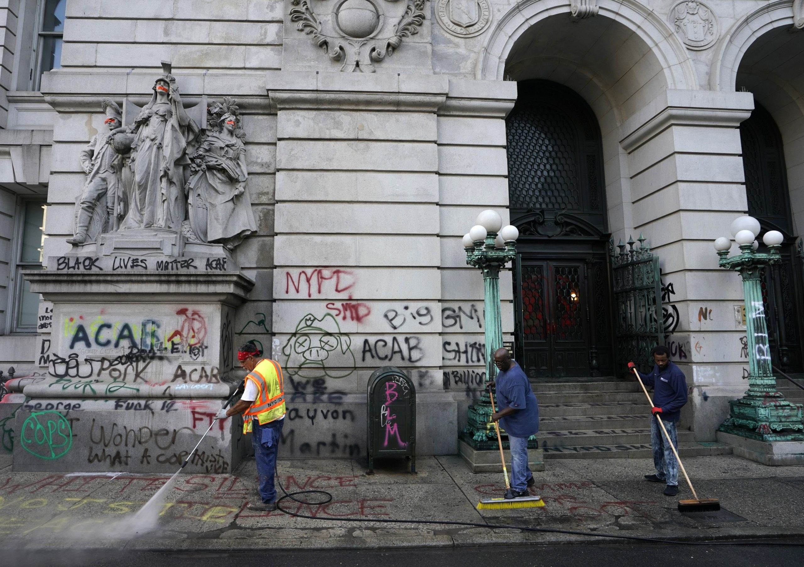 Sanitation workers clean up graffiti on July 22, 2020, after the Occupy City Hall protesters were cleared overnight by police - New York police removed the remaining Occupy City Hall protesters out of a month-long encampment. The protesters demanded a cut of at least $1 billion from the NYPD budget. The City Council approved the reform and Mayor Bill de Blasio signed into law. (Photo by TIMOTHY A. CLARY / AFP) (Photo by TIMOTHY A. CLARY/AFP via Getty Images)