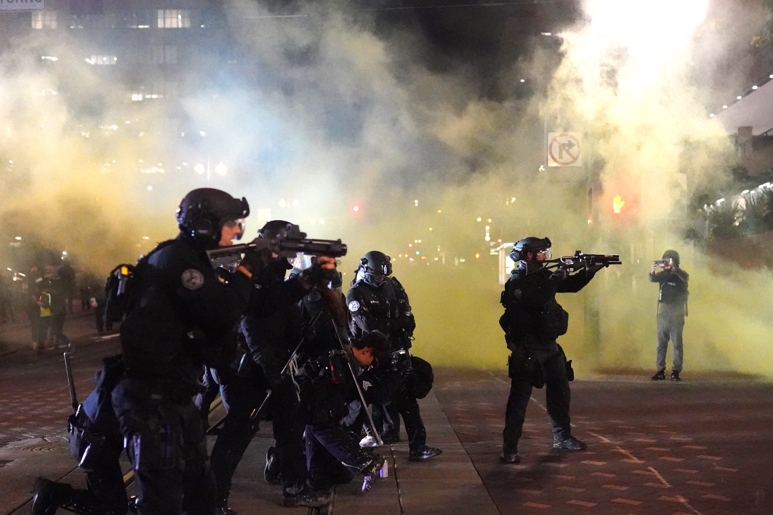 PORTLAND, OR - AUGUST 25: Portland police officers fires less lethal rounds through smoke while dispersing a crowd of about 150 people from Portland City Hall on August 25, 2020 in Portland, Oregon. Crowds chanted in support of Kenosha Wisconsin on the 90th night of protests Tuesday, where demonstrations have continued for days following the police shooting of Jacob Blake. (Photo by Nathan Howard/Getty Images)