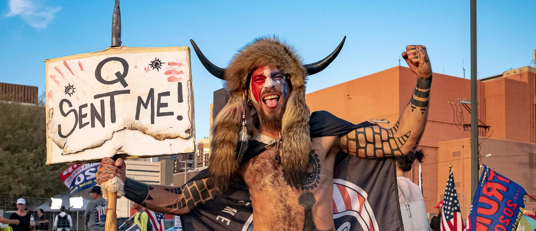 Jake Angeli, 33, aka Yellowstone Wolf, from Phoenix, holds a QAnon sign, as he presents himself as a shamanist and consultant for the Trump supporters gathered in front of the Maricopa County Election Department where ballots are counted after the US presidential election in Phoenix, Arizona, on November 5, 2020. - President Donald Trump erupted on November 5 in a tirade of unsubstantiated claims that he has been cheated out of winning the US election as vote counting across battleground states showed Democrat Joe Biden steadily closing in on victory. (Photo by OLIVIER TOURON / AFP) (Photo by OLIVIER TOURON/AFP via Getty Images)