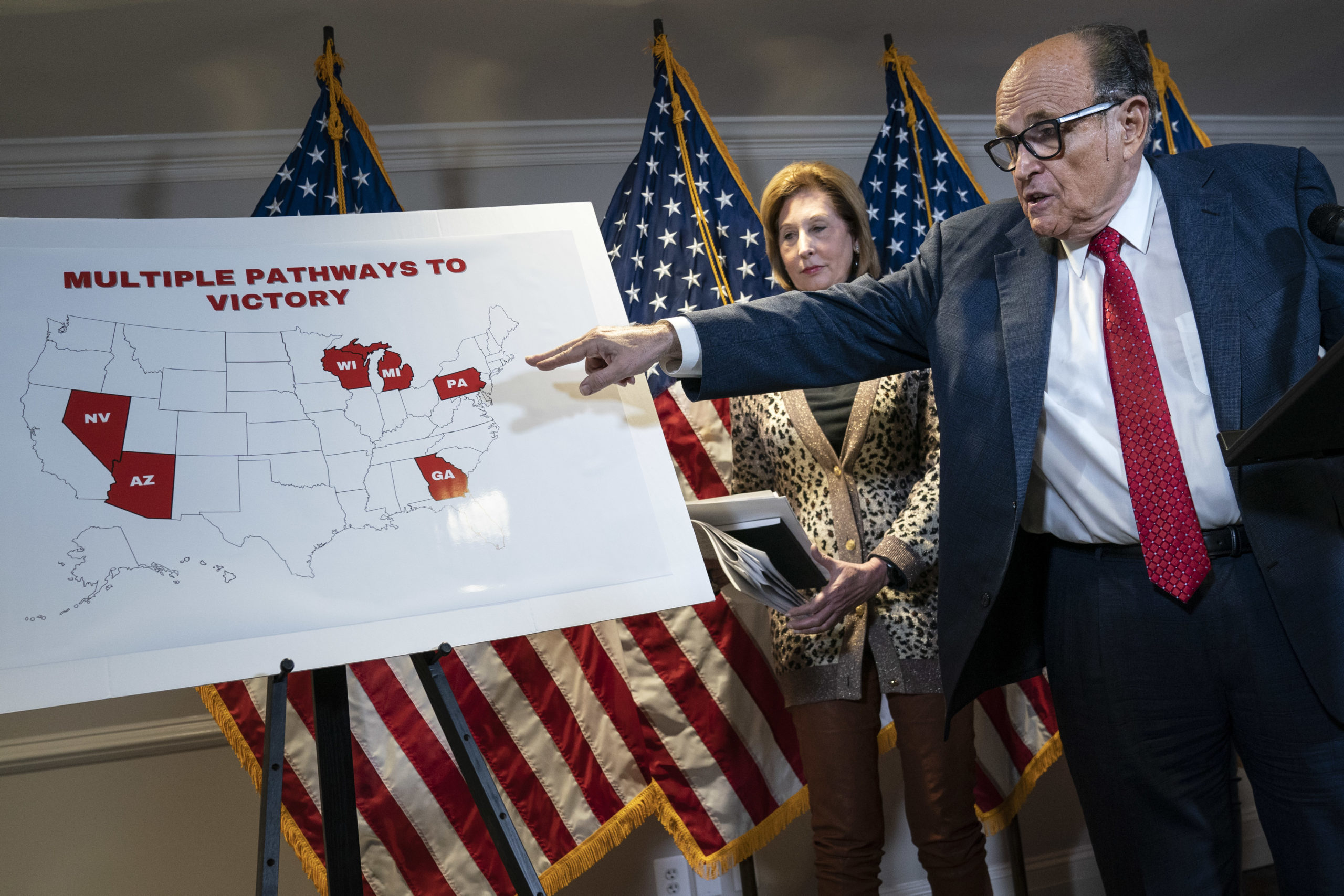 Alongside Sidney Powell, Rudy Giuliani points to a map as he speaks to the press about various lawsuits related to the 2020 election. (Drew Angerer/Getty Images)