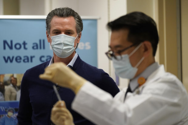 LOS ANGELES, CALIFORNIA - DECEMBER 14: Gov. Gavin Newsom watches as the Pfizer-BioNTech COVID-19 vaccine is prepared by Director of Inpatient Pharmacy David Cheng at Kaiser Permanente Los Angeles Medical Center on December 14, 2020 in Los Angeles, California. The first doses of the vaccine are being administered to frontline workers in hospitals across the country today. (Photo by Jae C. Hong-Pool/Getty Images)