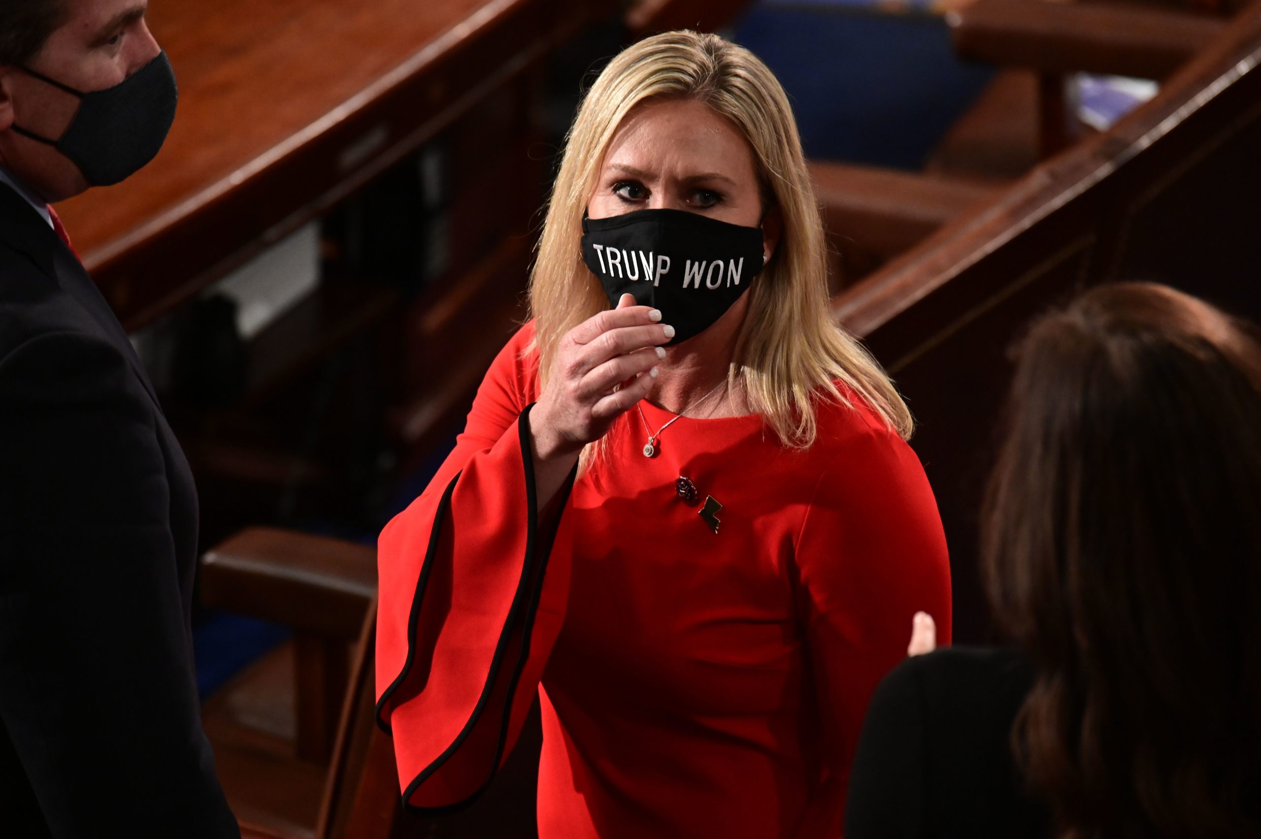 """US Rep. Marjorie Taylor Greene (R-GA) wears a """"Trump Won"""" face mask as she arrives on the floor of the House to take her oath of office as a newly elected member of the 117th House of Representatives in Washington, DC on January 3, 2021. (Photo by ERIN SCOTT / POOL / AFP) (Photo by ERIN SCOTT/POOL/AFP via Getty Images)"""