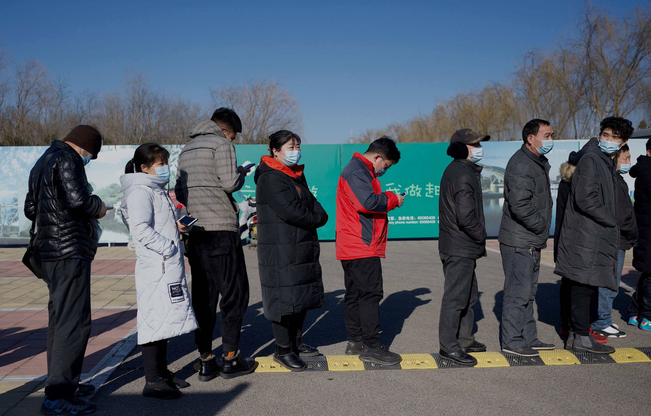 People wait to board shuttle buses to a COVID-19 coronavirus vaccine center in Beijing on January 5, 2021, as China races to innoculate millions before the Chinese New Year Mass travel season in February. (Photo by Noel Celis / AFP) (Photo by NOEL CELIS/AFP via Getty Images)