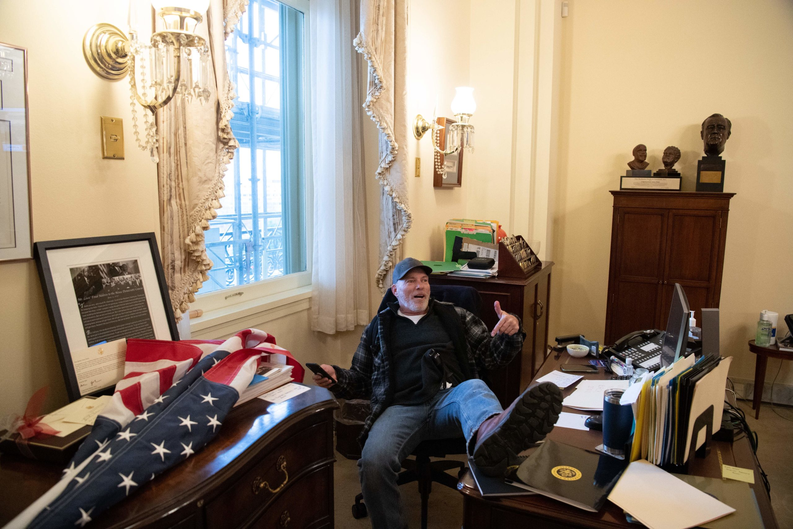 A supporter of US President Donald Trump sits inside the office of US Speaker of the House Nancy Pelosi as he protest inside the US Capitol in Washington, DC, January 6, 2021. - Demonstrators breeched security and entered the Capitol as Congress debated the a 2020 presidential election Electoral Vote Certification. (Photo by Saul Loeb/AFP via Getty Images)