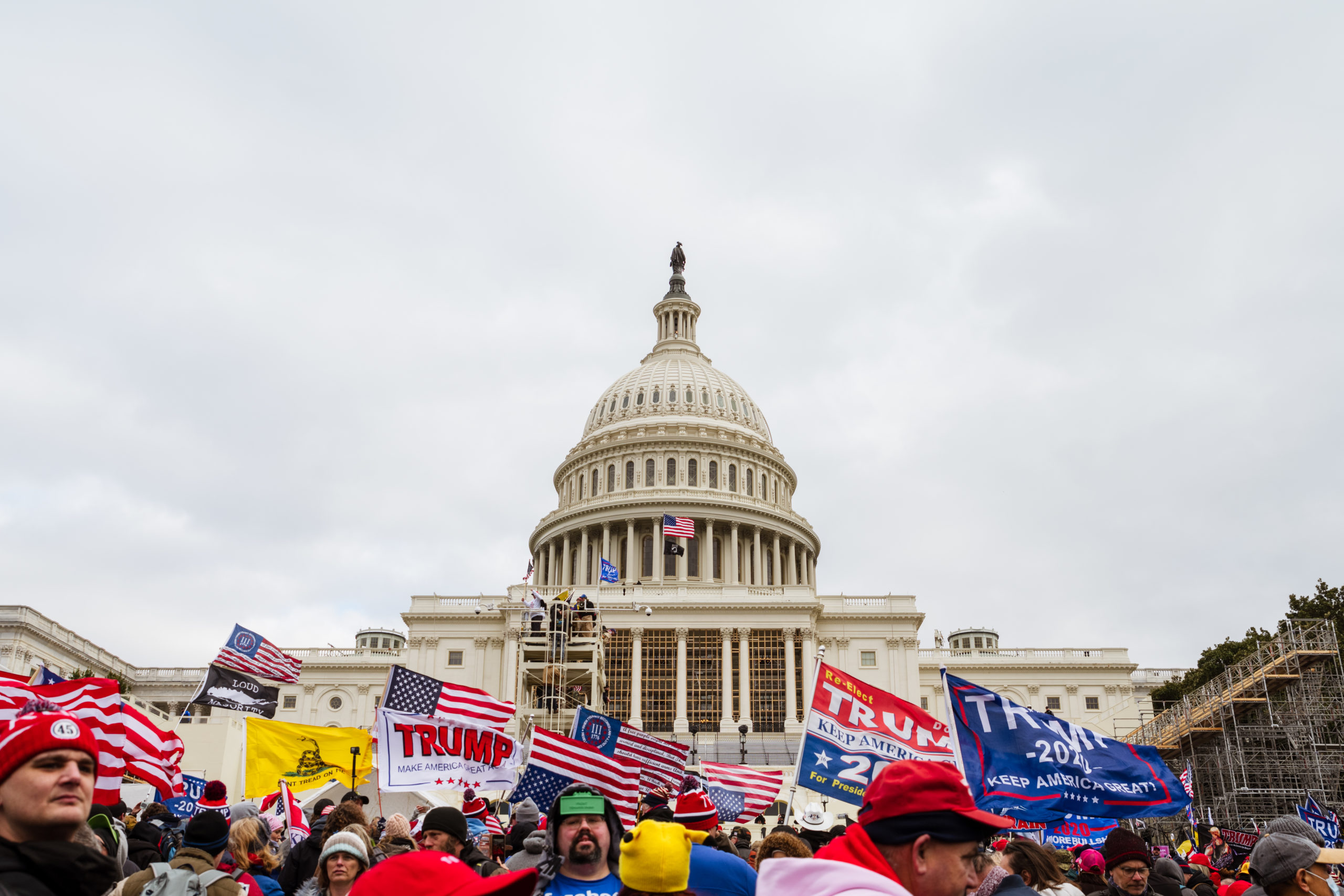 A group of pro-Trump rioters raise signs and flags on the grounds of the Capitol Building on January 6, 2021 in Washington, DC. (Jon Cherry/Getty Images)