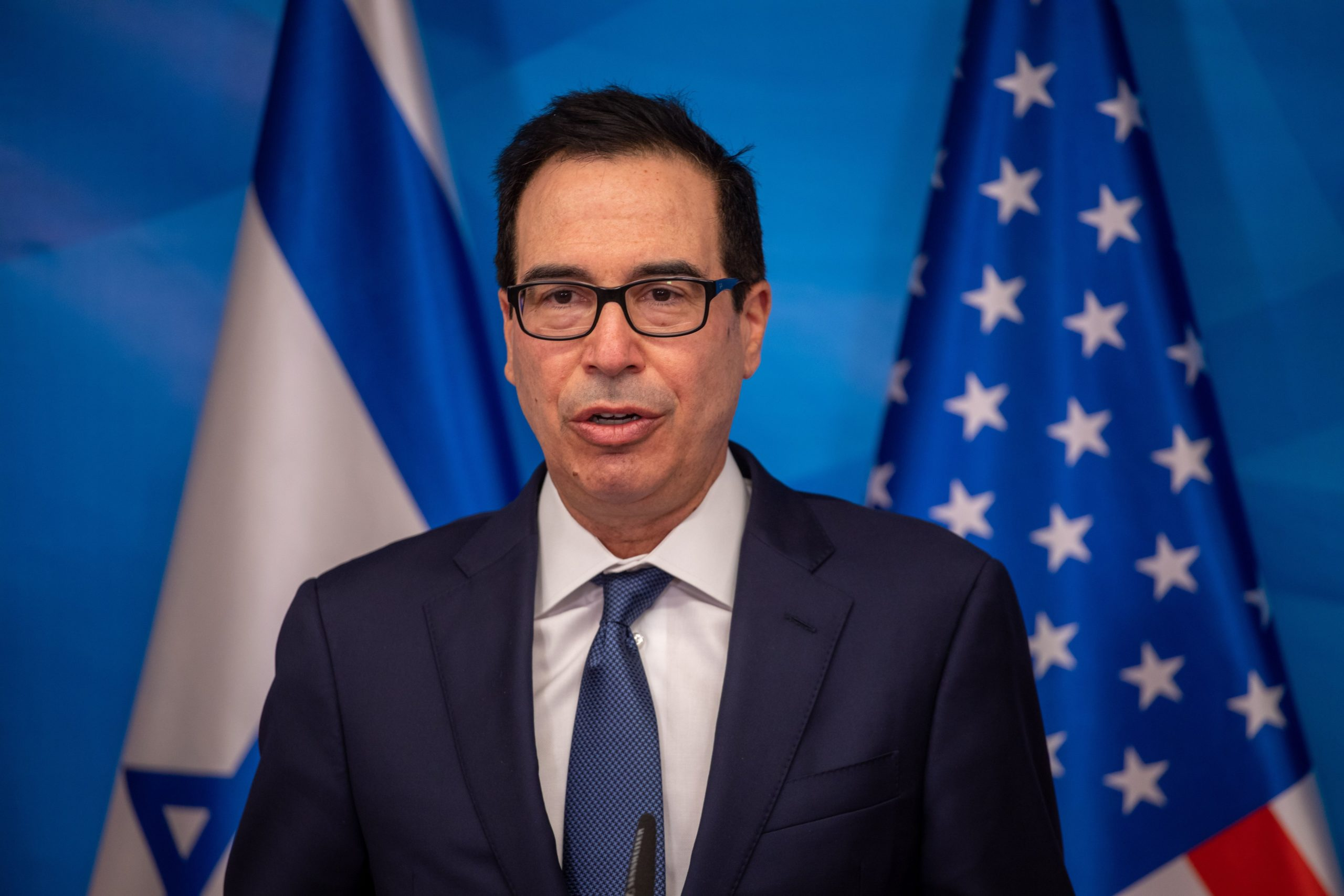 """US Treasury Secretary Steven Mnuchin gives a statement following his meeting meeting with the Israeli prime minister in Jerusalem, on January 7, 2021. - Israeli Prime Minister Benjamin Netanyahu condemned as """"disgraceful"""" violence by supporters of his staunch ally President Donald Trump at the US Capitol building. He made the comments in Jerusalem alongside Munchin, who called the storming of the Capitol """"unacceptable"""". (Photo by EMIL SALMAN/POOL/AFP via Getty Images)"""