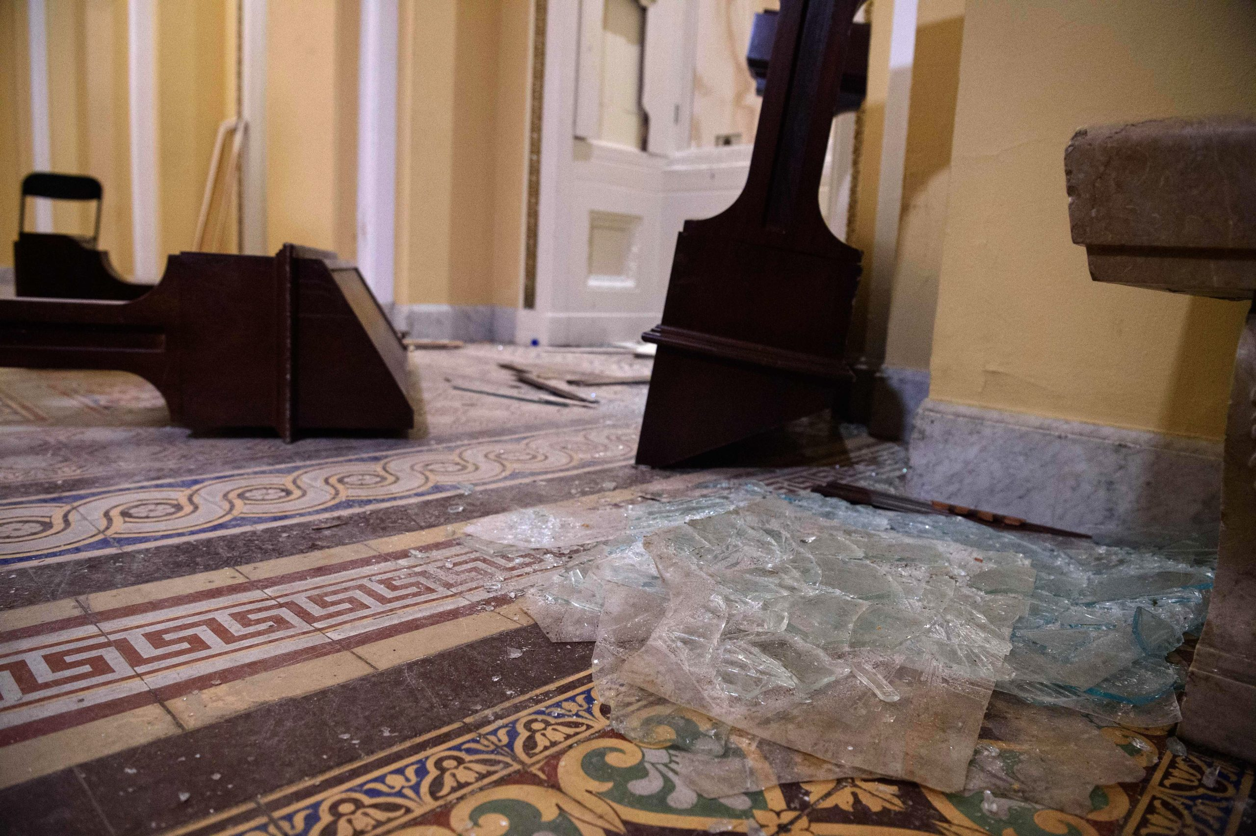 Overturned furniture and broken glass litter a hallway of the US Capitol in Washington, DC, on January 7, 2021, one day after supporters of outgoing President Donald Trump stormed the building. (Photo by Nicholas Kamm/AFP via Getty Images)