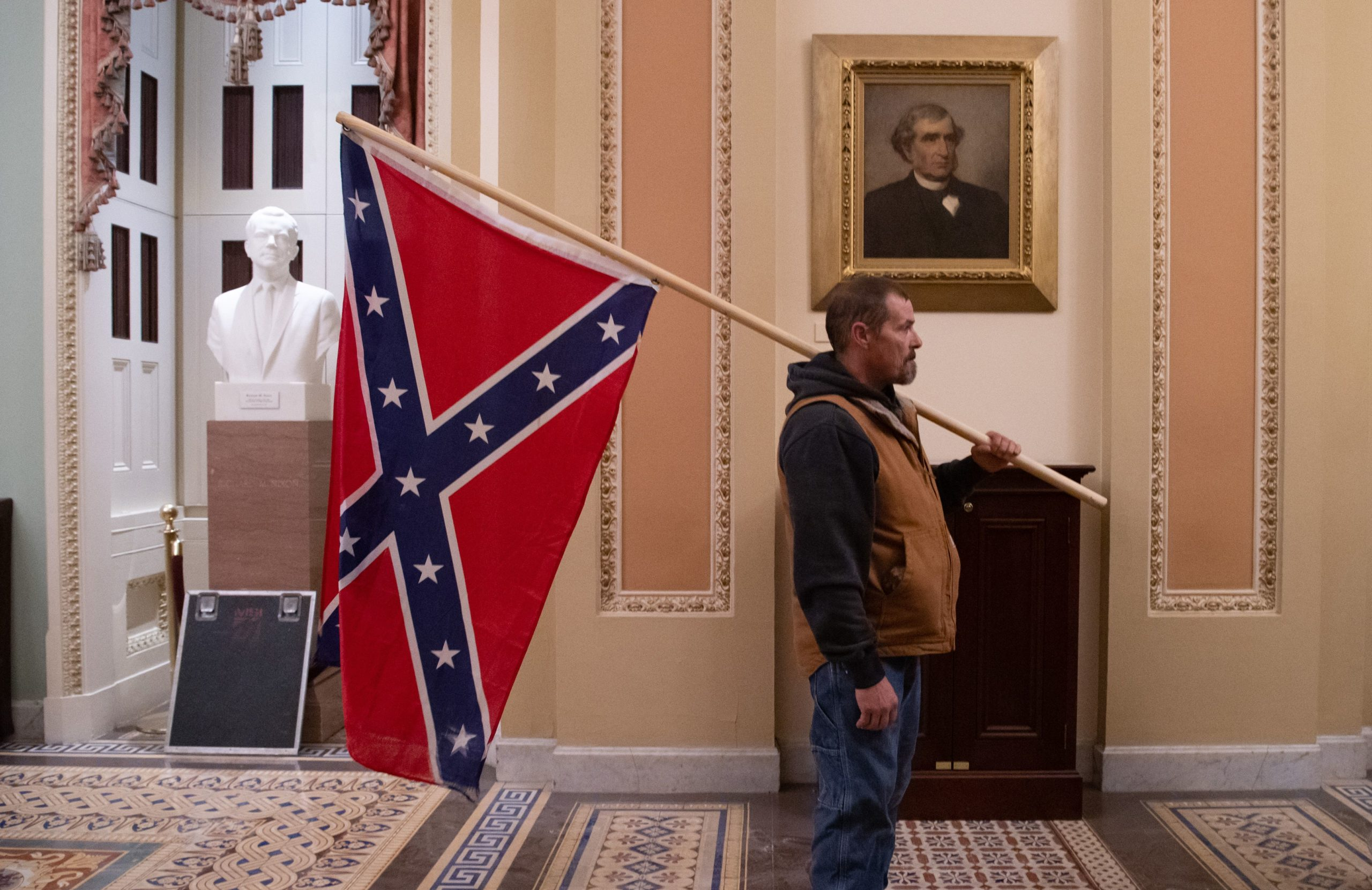 A supporter of US President Donald Trump holds a Confederate flag outside the Senate Chamber during a protest after breaching the US Capitol in Washington, DC, January 6, 2021. - The demonstrators breeched security and entered the Capitol as Congress debated the 2020 presidential election Electoral Vote Certification. (Photo by Saul Loeb/AFP via Getty Images)