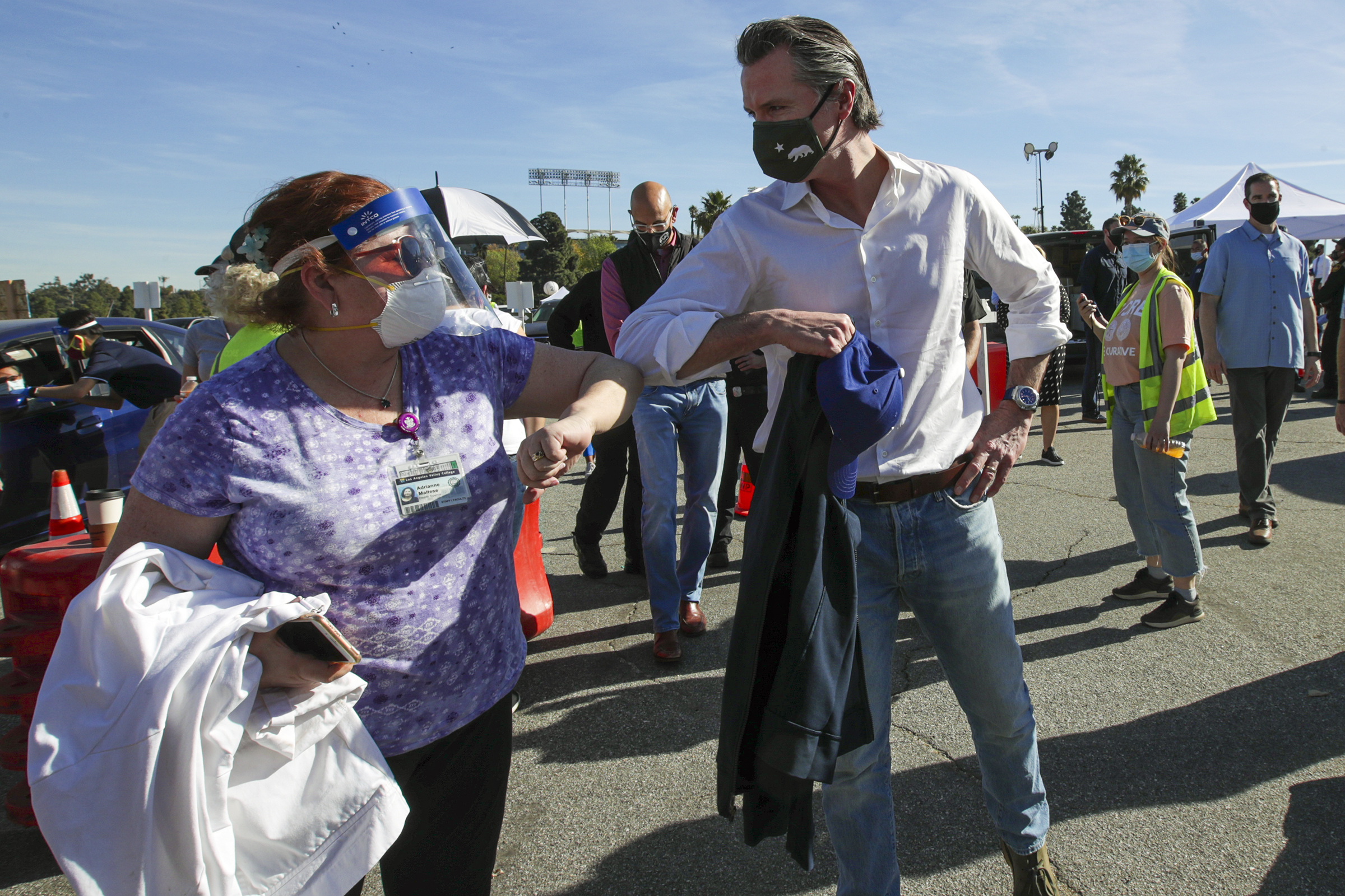 California Gov. Gavin Newsom is greeted by a healthcare worker at the launch of a mass coronavirus vaccination site at Dodger Stadium on Jan. 15 in Los Angeles, California. (Irfan Khan/Pool/AFP via Getty Images)