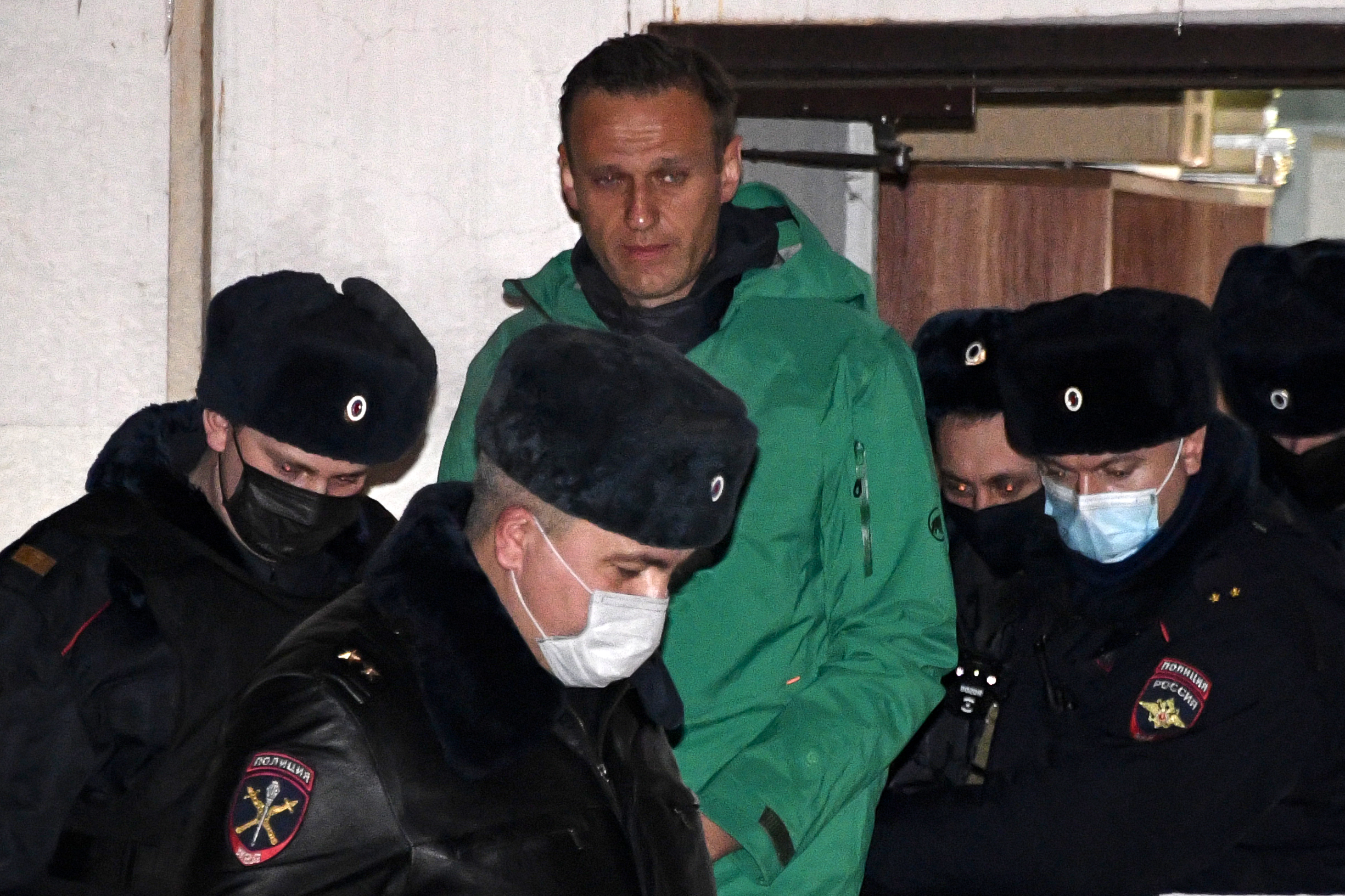 Russian opposition leader Alexei Navalny is escorted out of a police station in Khimki, outside Moscow, following Monday's court ruling that ordered him jailed for 30 days. (Alexander Nemenov/AFP via Getty Images)