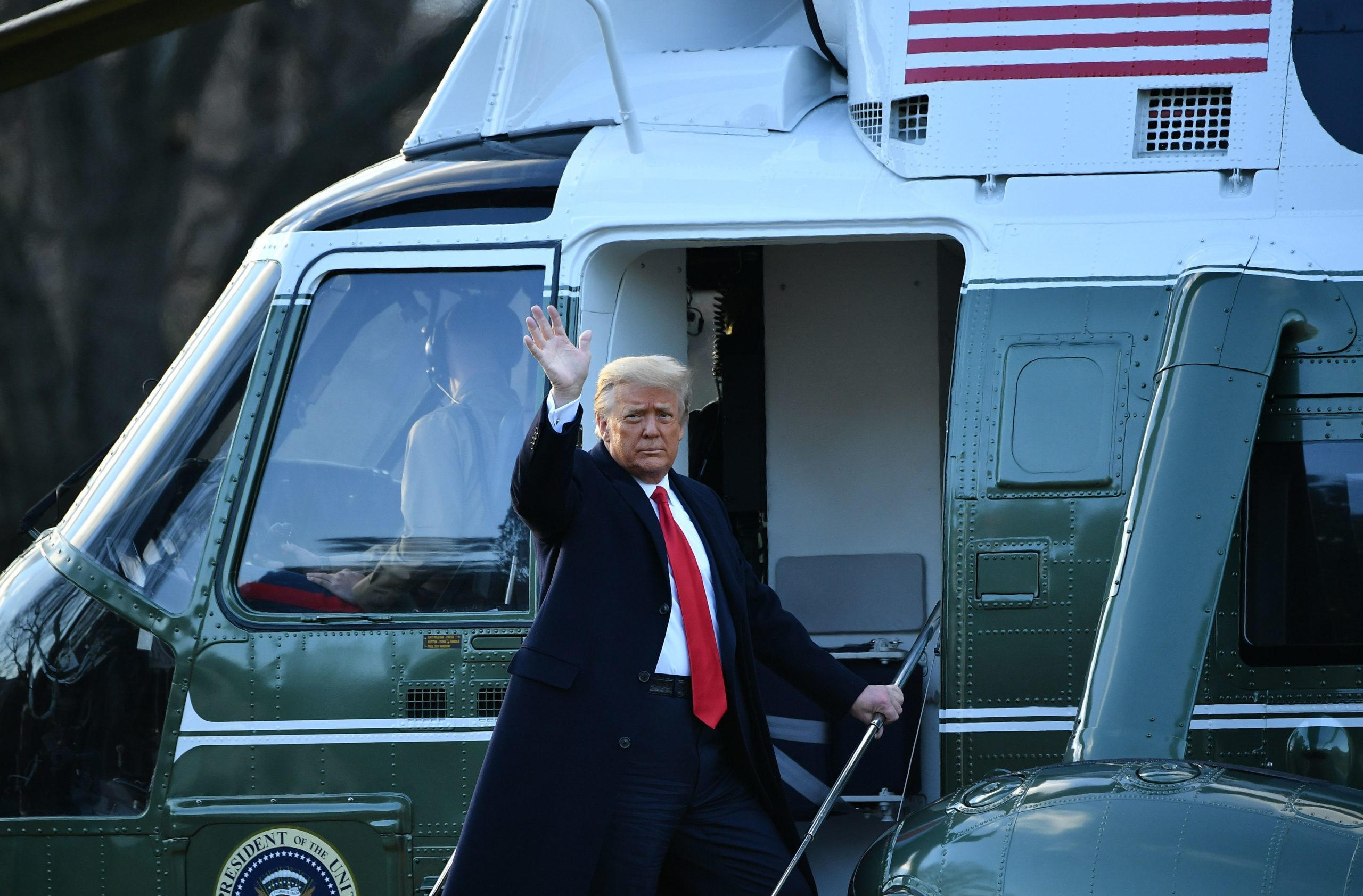 Outgoing US President Donald Trump waves as he boards Marine One at the White House in Washington, DC, on January 20, 2021. (Photo by MANDEL NGAN/AFP via Getty Images)