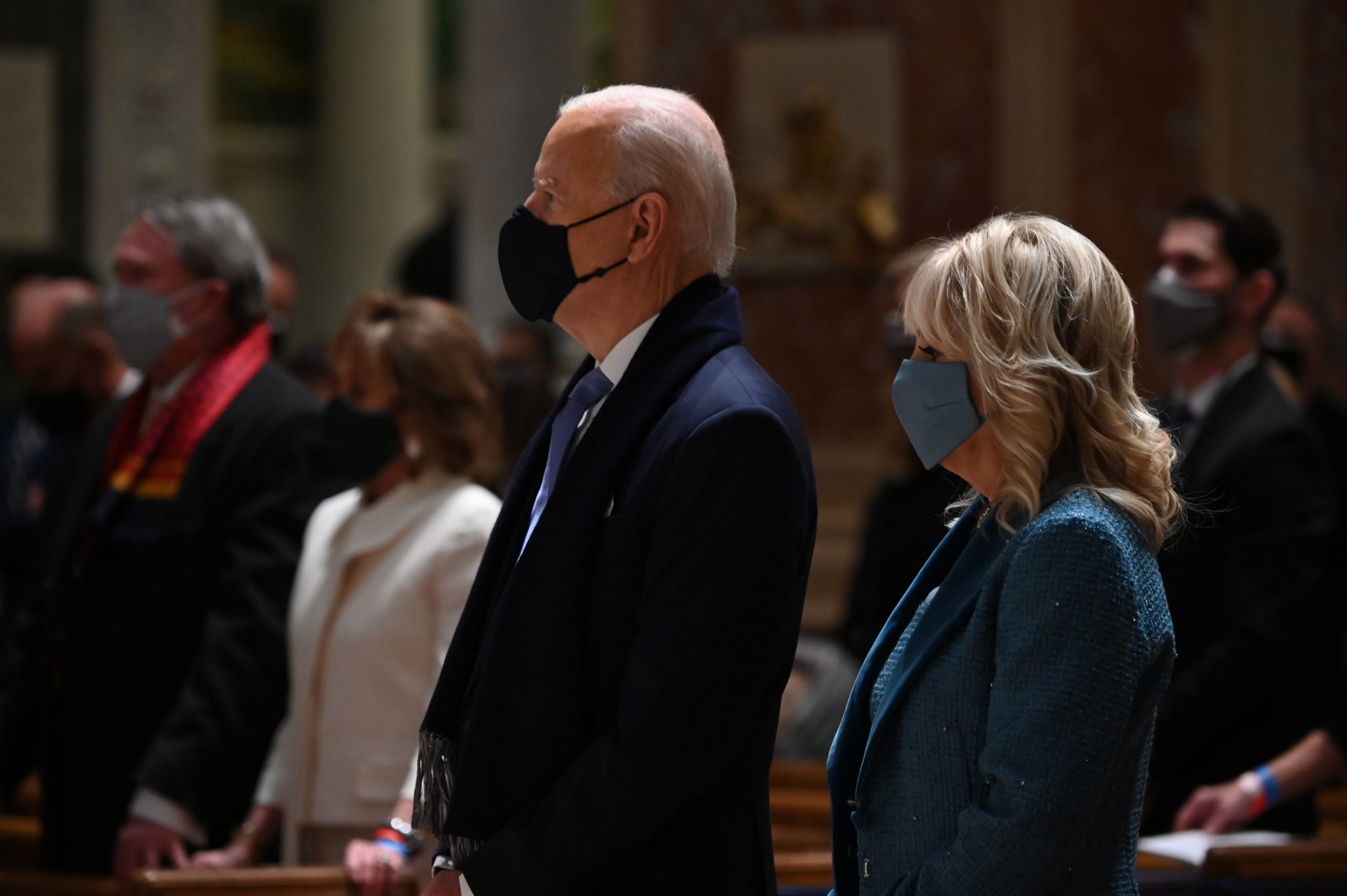 TOPSHOT - US President-elect Joe Biden (C) and incoming First Lady Jill Biden attend Mass at the Cathedral of St. Matthew the Apostle in Washington, DC, on January 20, 2021. - Biden is to be sworn in as the 46th US President at the US Capitol. (Photo by JIM WATSON / AFP) (Photo by JIM WATSON/AFP via Getty Images)