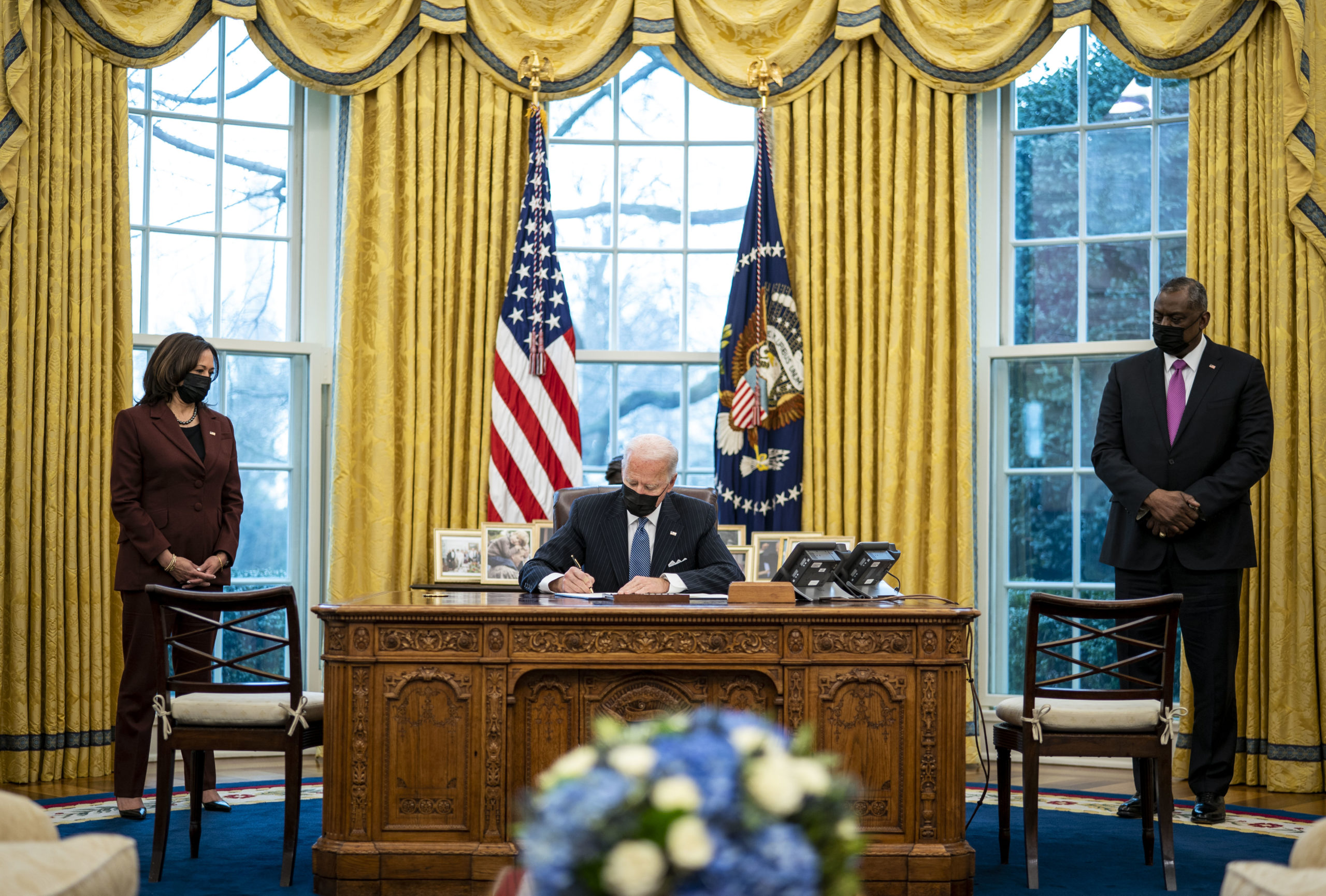 President Joe Biden signs an executive order in the Oval Office on Monday. (Doug Mills-Pool/Getty Images)