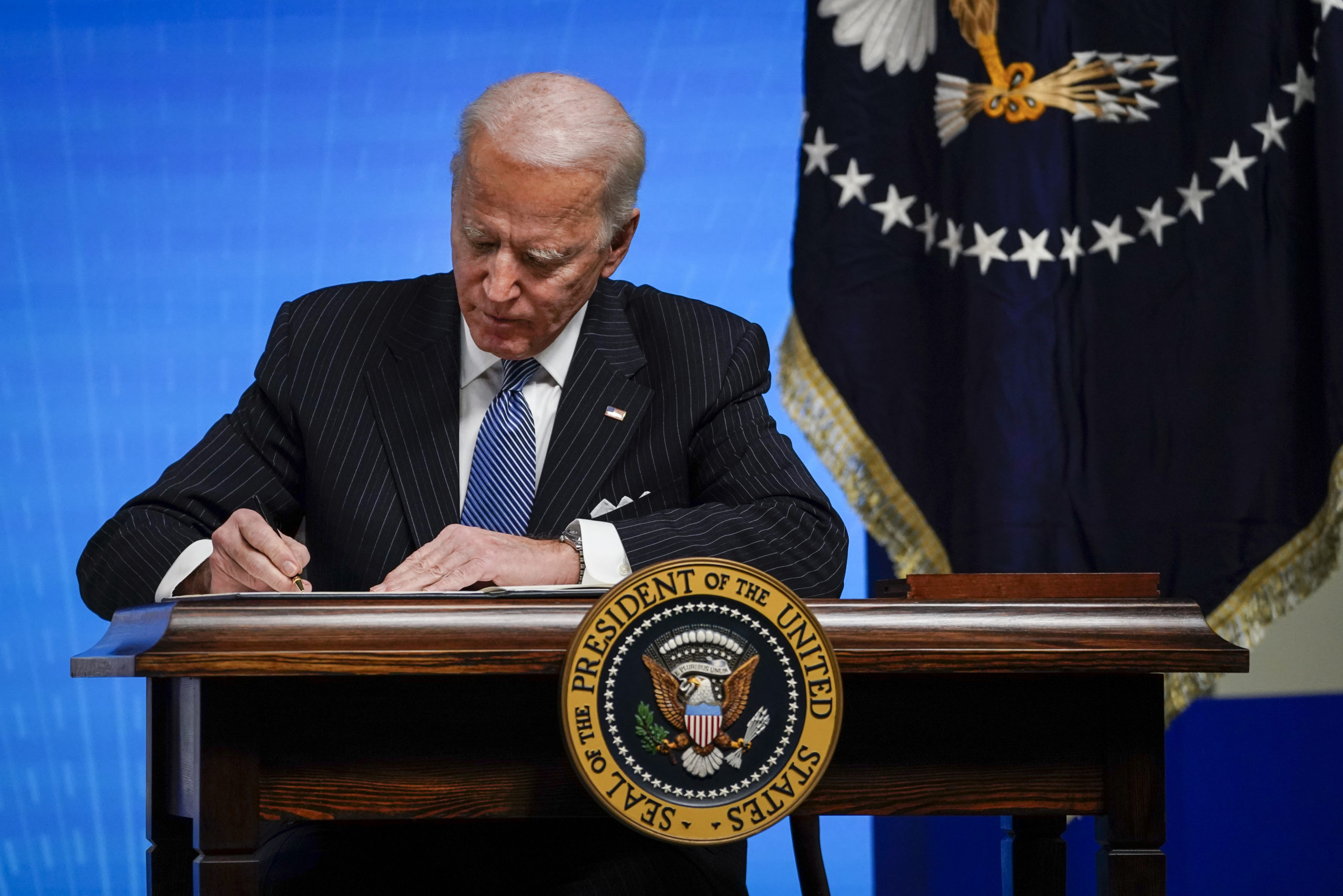 President Joe Biden signs an executive order at the White House on Jan. 25. (Drew Angerer/Getty Images)