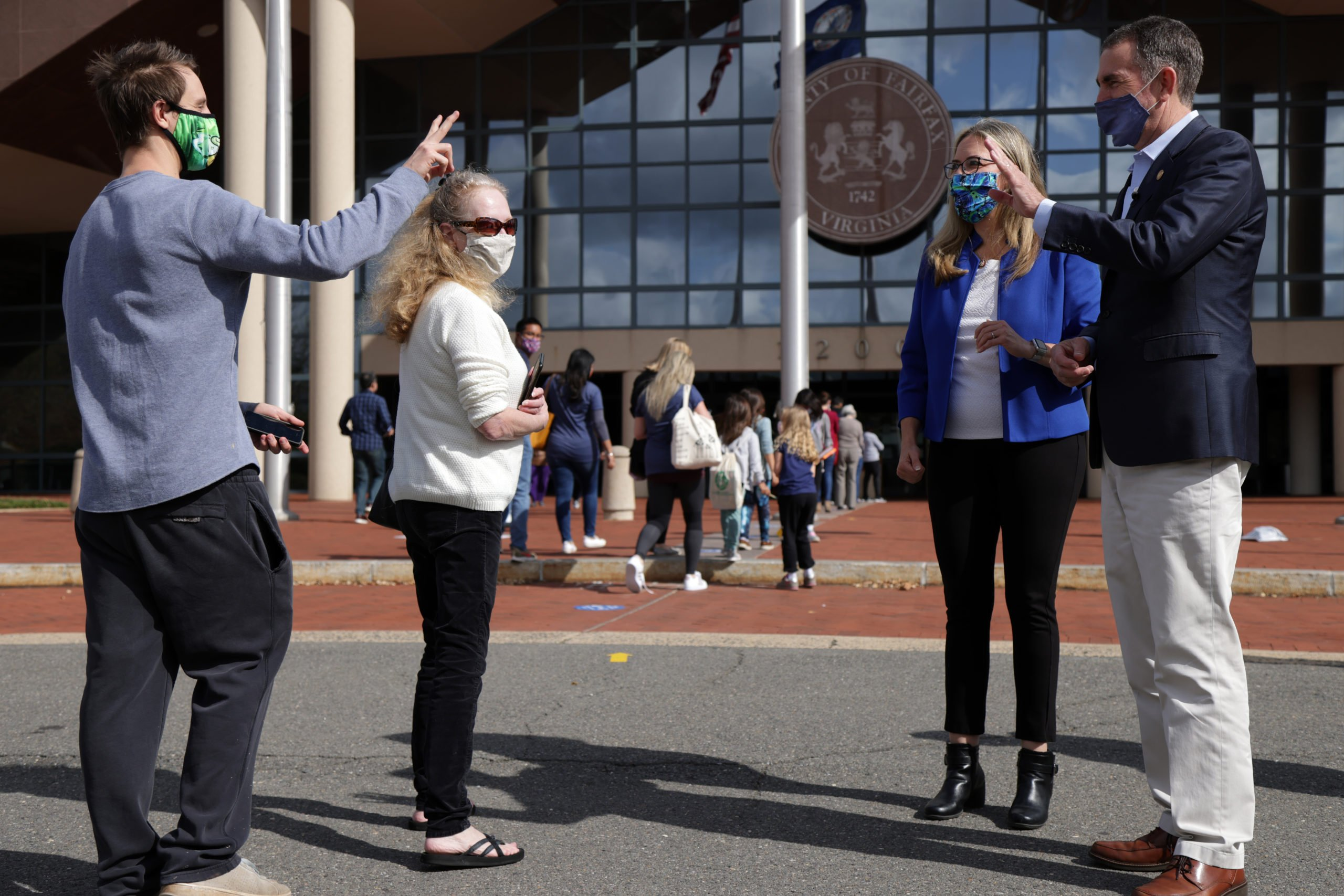 Virginia Gov. Ralph Northam and Rep. Jennifer Wexton greet voters outside an early voting location at Fairfax County Government Center on Oct. 19 in Fairfax, Virginia. (Alex Wong/Getty Images)