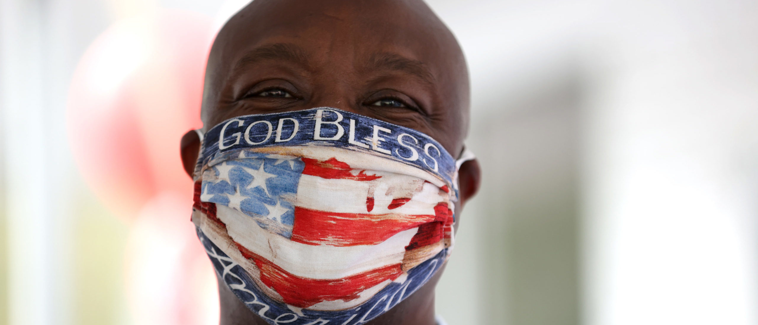 """DOUGLASVILLE, GEORGIA - OCTOBER 28: U.S. Sen. Tim Scott (R-SC) wears a face mask that reads """"God Bless America"""" during a campaign event with U.S. Sen. Kelly Loeffler (R-GA) at Metro Garage Door on October 28, 2020 in Douglasville, Georgia. (Photo by Justin Sullivan/Getty Images)"""