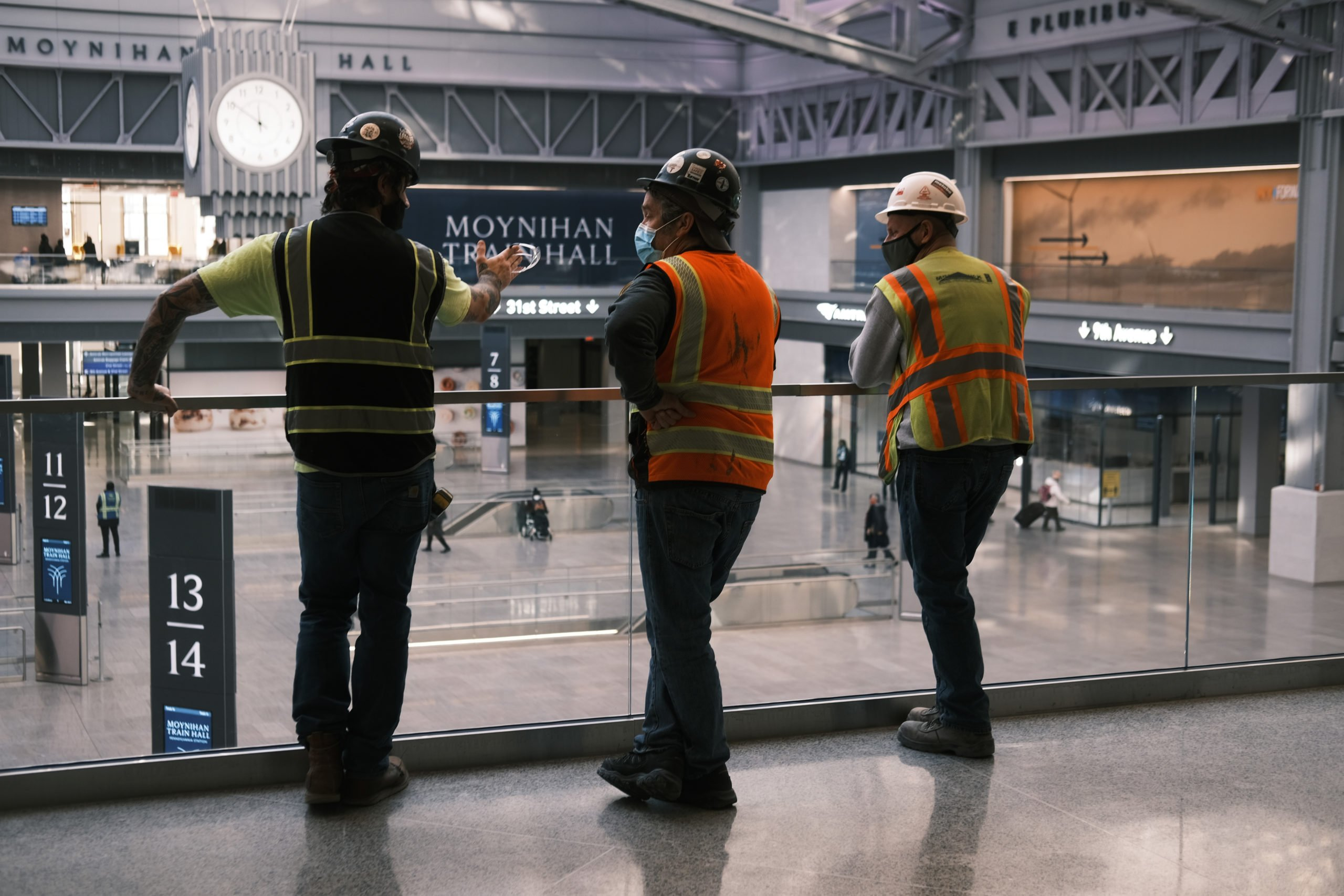 Workers involved in the construction of the newly opened Moynihan Train Hall in New York City look over the main hall on Jan. 4. (Spencer Platt/Getty Images)