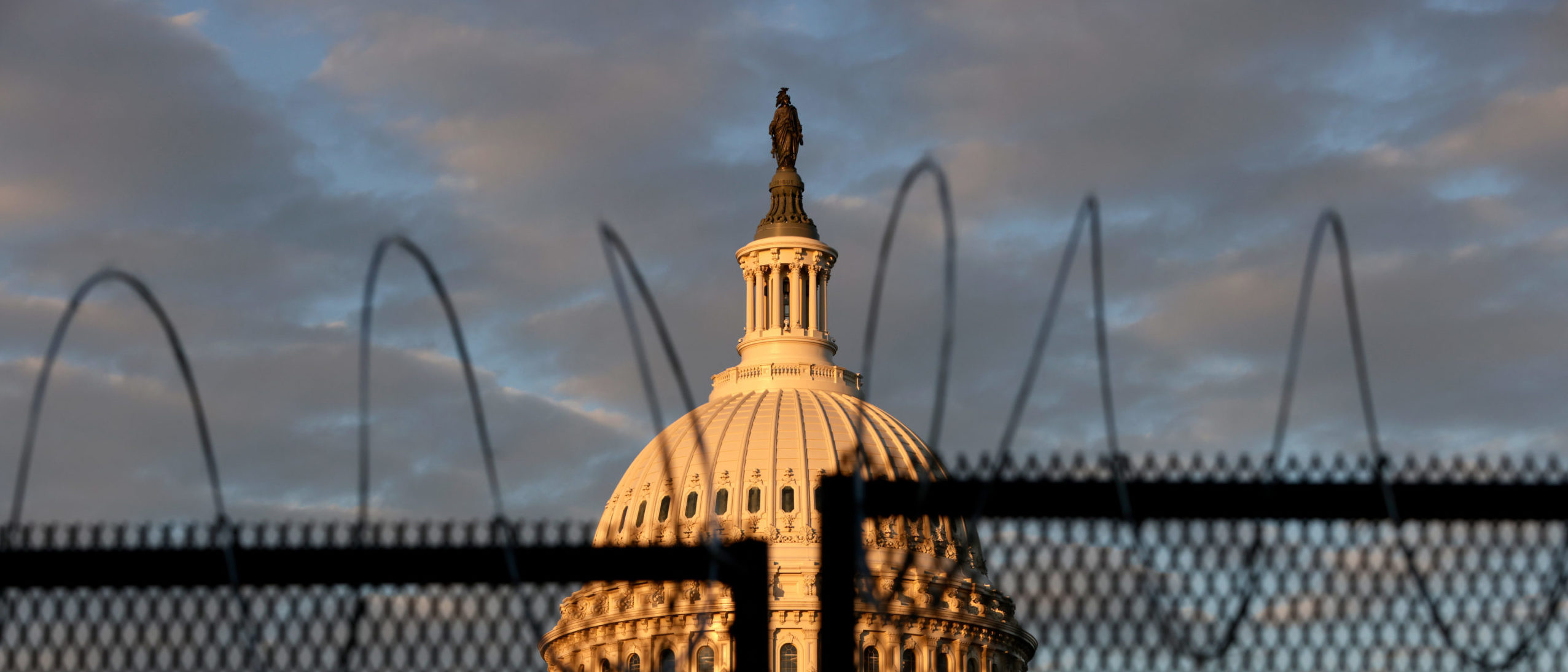WASHINGTON, DC - JANUARY 16: The U.S. Capitol is seen behind a fence with razor wire during sunrise on January 16, 2021 in Washington, DC. After last week's riots at the U.S. Capitol Building, the FBI has warned of additional threats in the nation's capital and in all 50 states. According to reports, as many as 25,000 National Guard soldiers will be guarding the city as preparations are made for the inauguration of Joe Biden as the 46th U.S. President. (Photo by Samuel Corum/Getty Images)