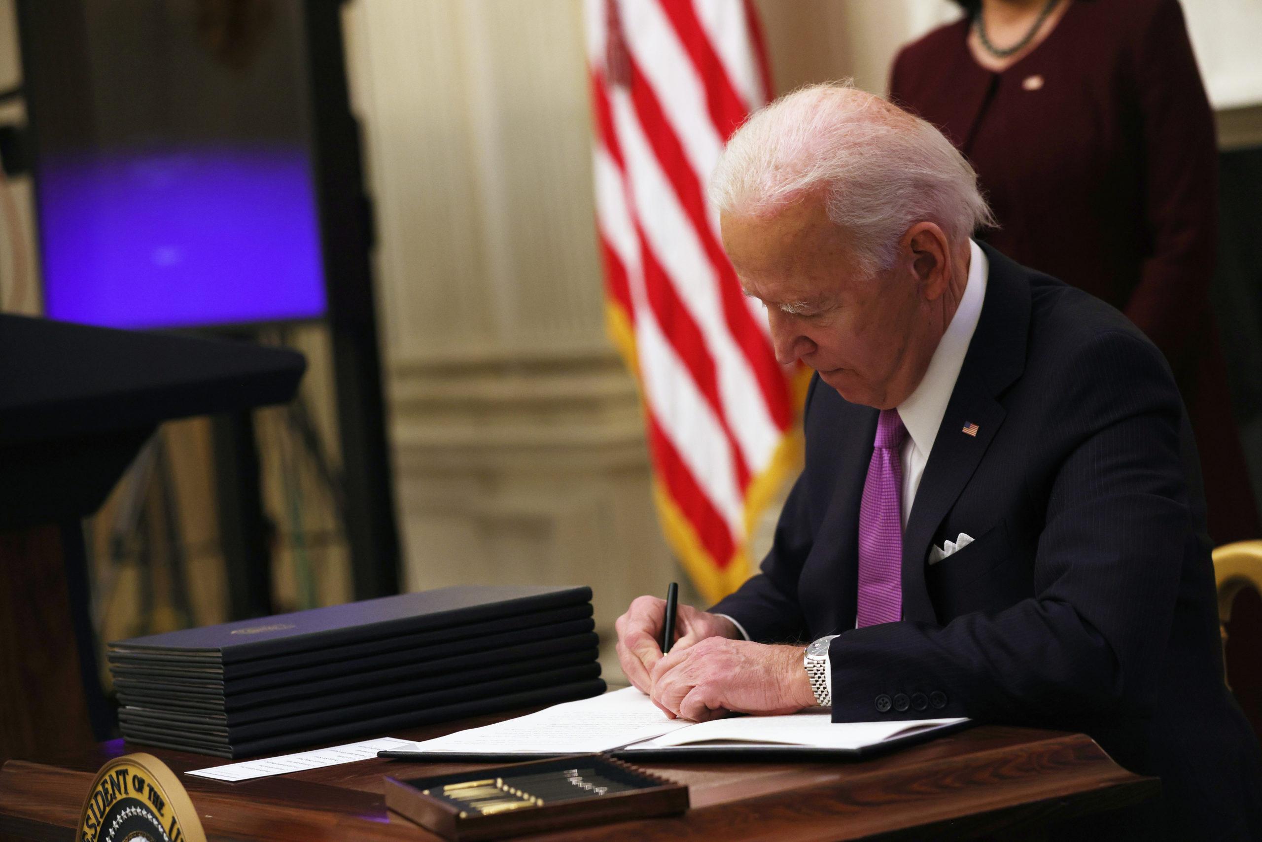 President Joe Biden signs an executive order on Jan. 21. (Alex Wong/Getty Images)