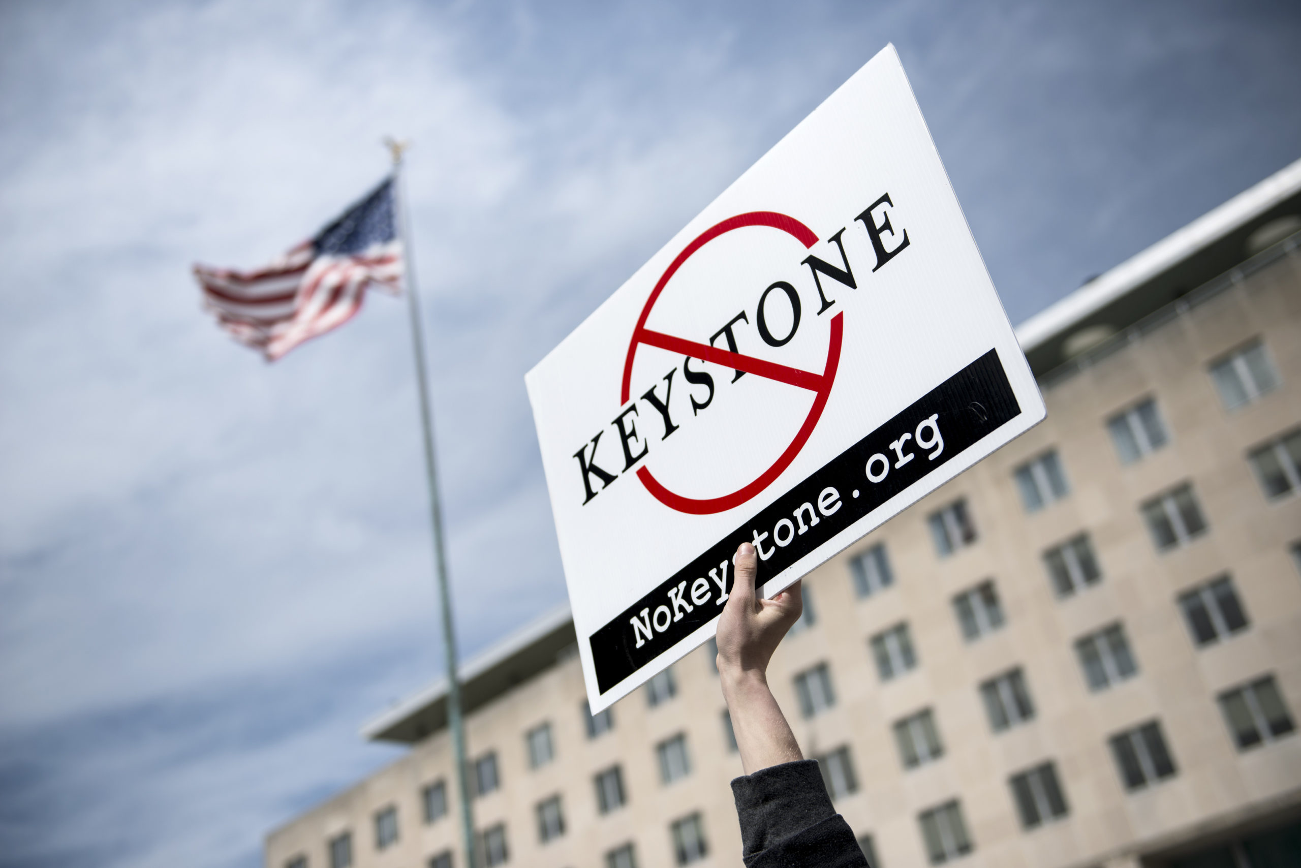 An activist holds up a sign outside the State Department during a protest of the Keystone XL pipeline on March 7, 2014 in Washington D.C. (Brendan Smialowski/AFP via Getty Images)