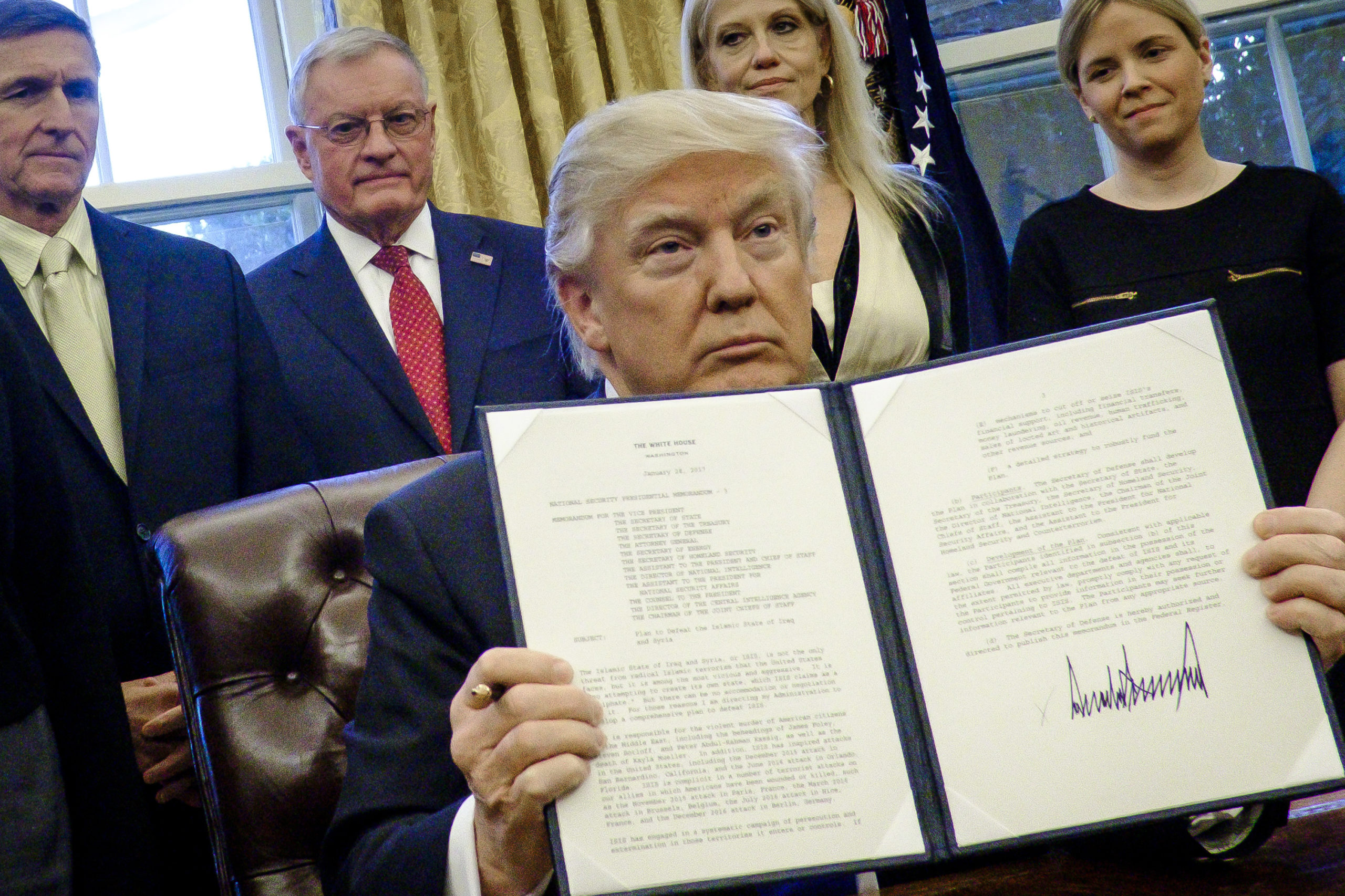 President Donald Trump holds up his executive order restricting lobbying in the Oval Office on Jan. 28, 2017. (Pete Marovich/Pool/Getty Images)